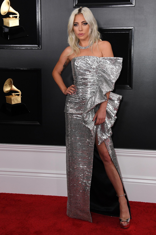 Lady Gaga en metalizado. La cantante apostó a un diseño strapless con gran tajo en la falda y . Completó su look con plataformas plateadas y gargantilla de brillantes