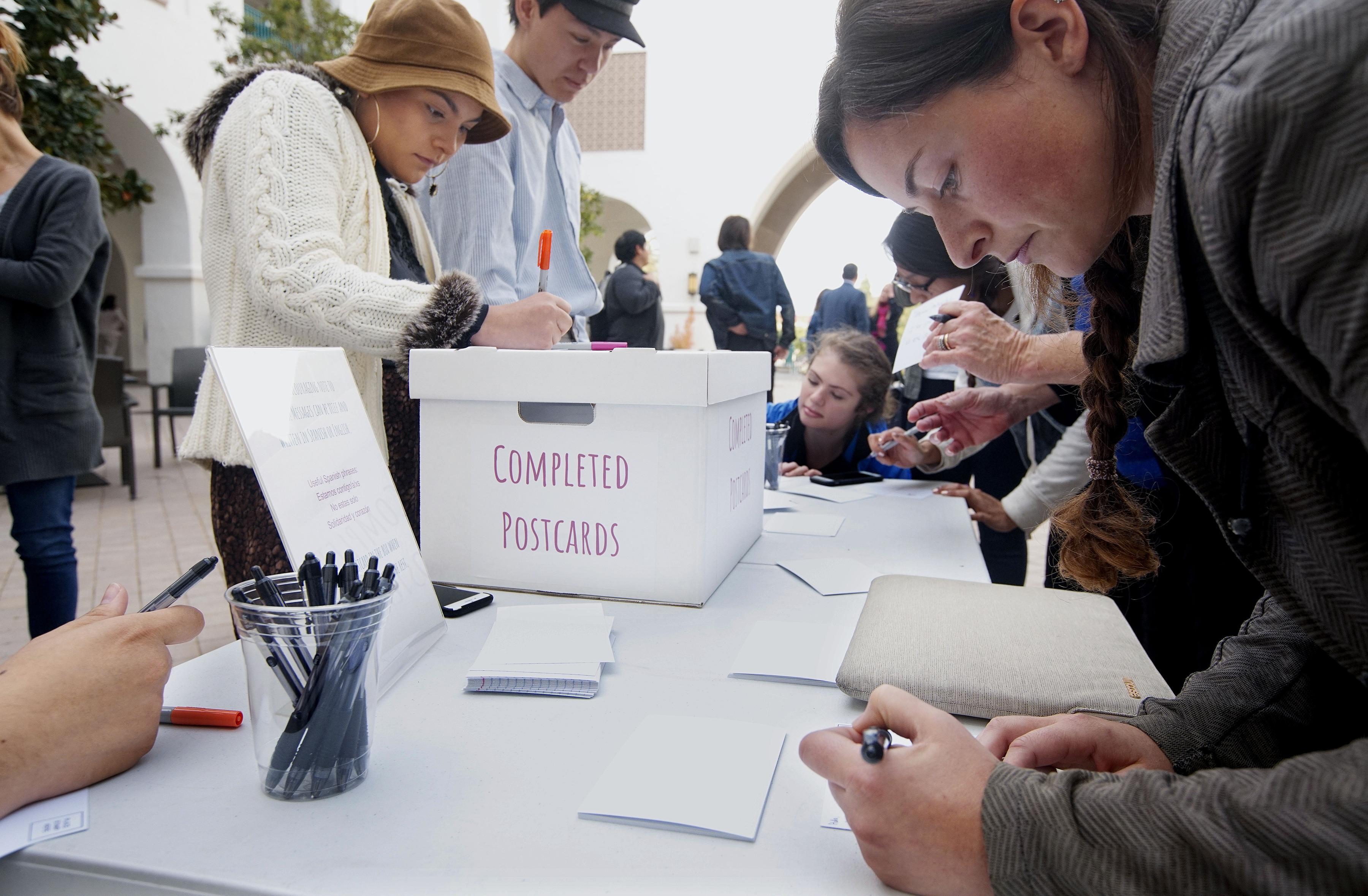 Un grupo de personas en la Universidad de San Diego escribe cartas a los migrantes. (Sandy Huffaker/The New York Times)