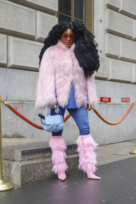 Yeti style en el tapado y botas. Para combinar con su cabellera tipo afro y sus gafas sixties de acetato colorado y la mini bag de peluche, el color rosa bebé fue el elegido para las plumas del tapado y las botas en punta y de taco aguja