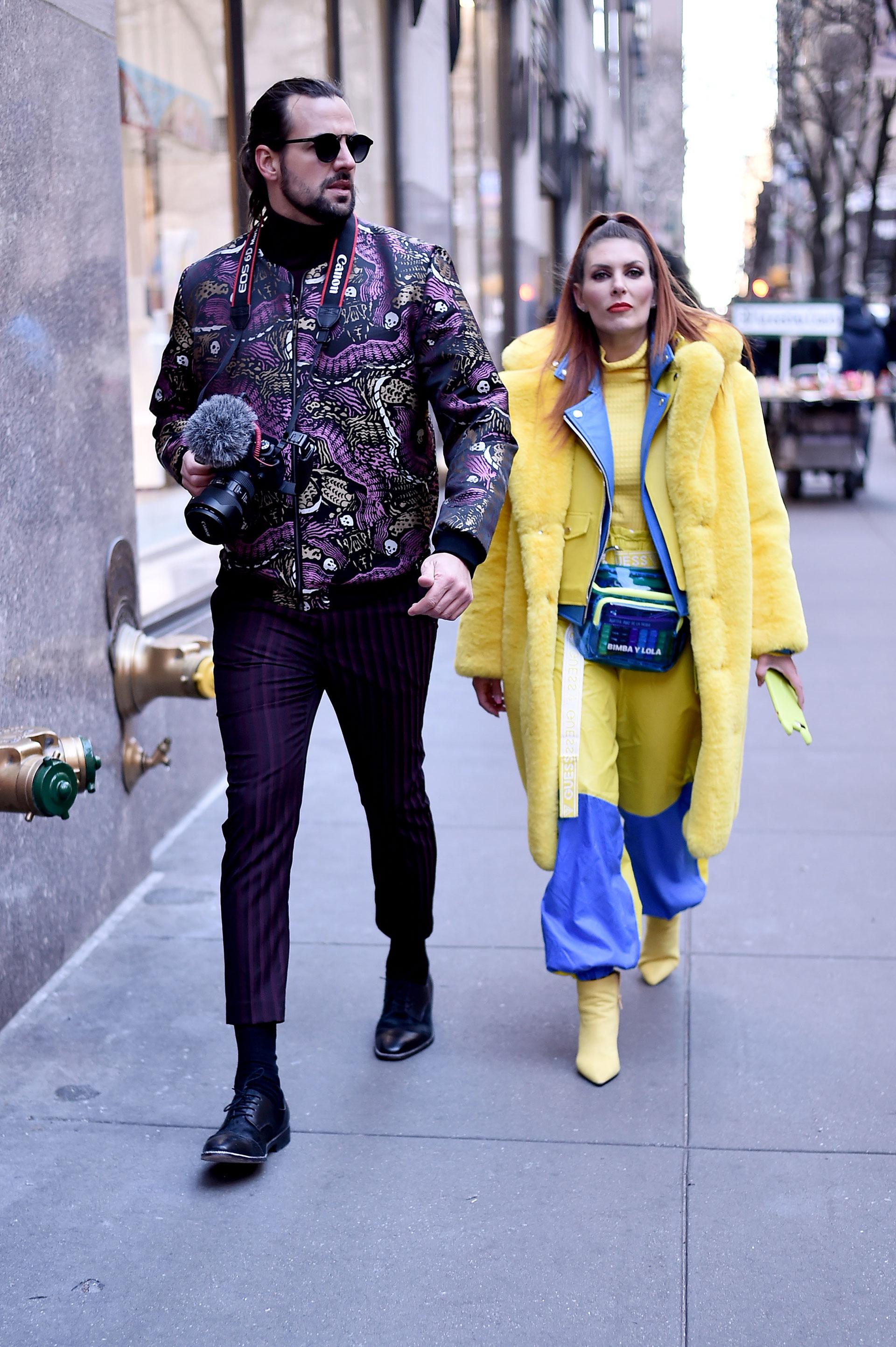 Dúo fashionista. Él con pantalón crop rayado de vestir en color púrpura, con zapatos acordonados y bomber estampada con animales. Ella con mix de texturas, piel, impermeable y cuero, todo en azul y amarillo. El detalle chic, la riñonera de pvc