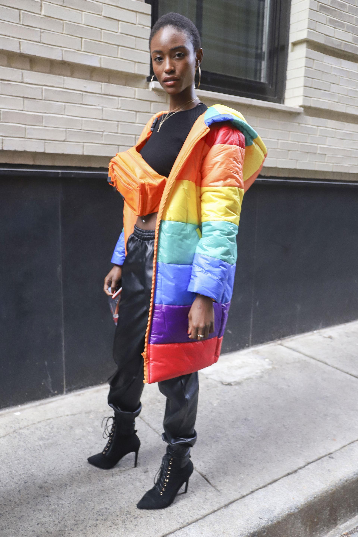 Las puffer jackets siguen vigentes. Multicolor, XL, con capucha y a la rodilla, el diseño que se luce por las calles de NY. Un conjunto de crop top negro y pantalón de cuero abullonado con booties acordonadas. ¿El detalle fashionista? La riñonera en naranja flúor