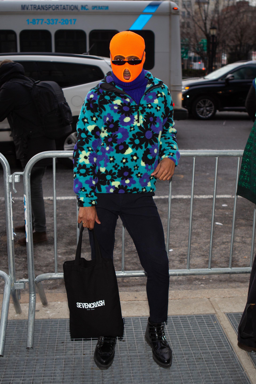 Polar estampado de flores y un pasamontaña en naranja flúor. Con sweater de cuello polera debajo y pantalón de vestir con borceguíes acharolados en punta