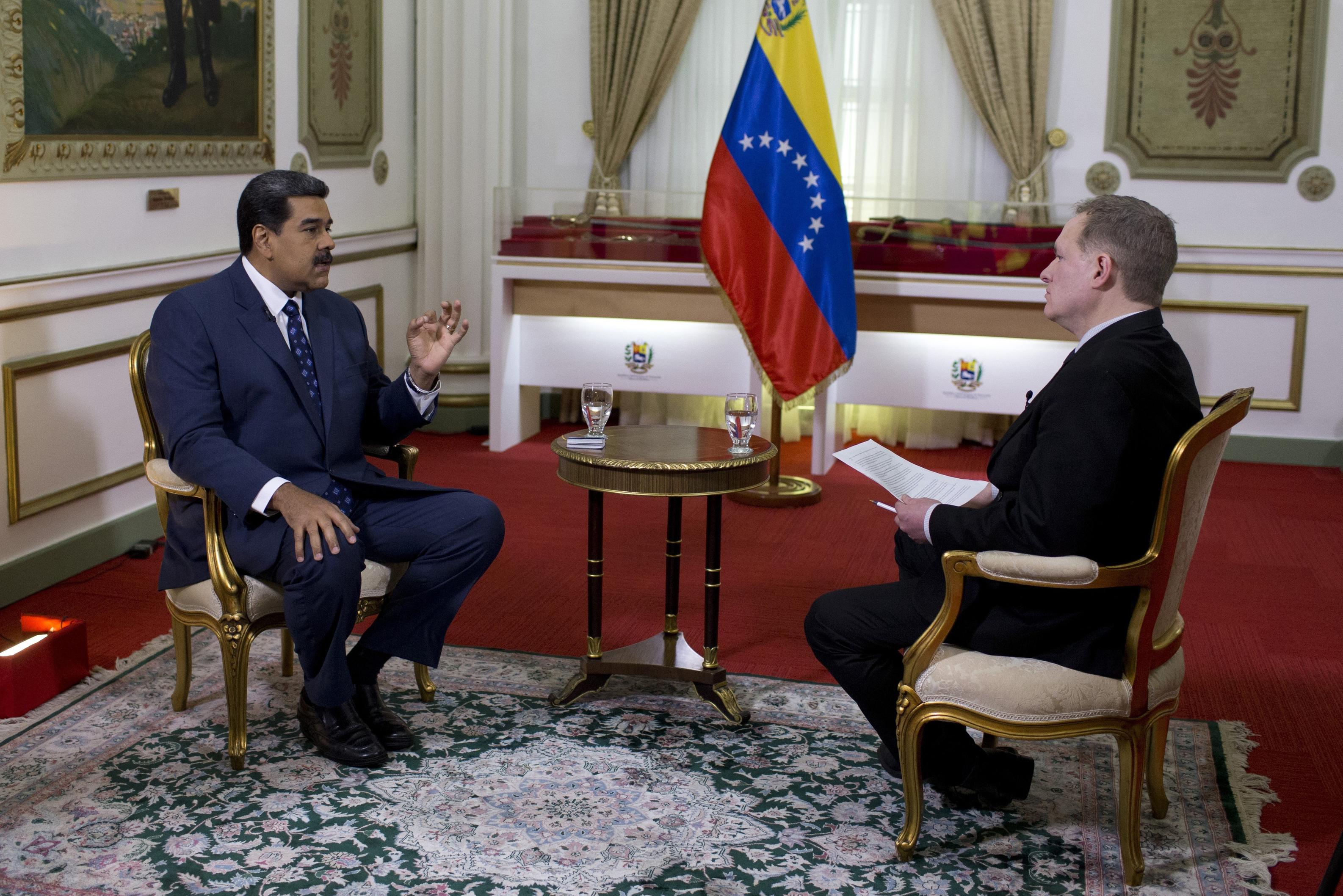 El presidente venezolano Nicolás Maduro, izquierda, habla durante una entrevista con Ian Phillips, vicepresidente de noticias internacionales de The Associated Press, en el Palacio de Miraflores en Caracas, Venezuela, el jueves 14 de febrero de 2019. (AP Foto/Ariana Cubillos)