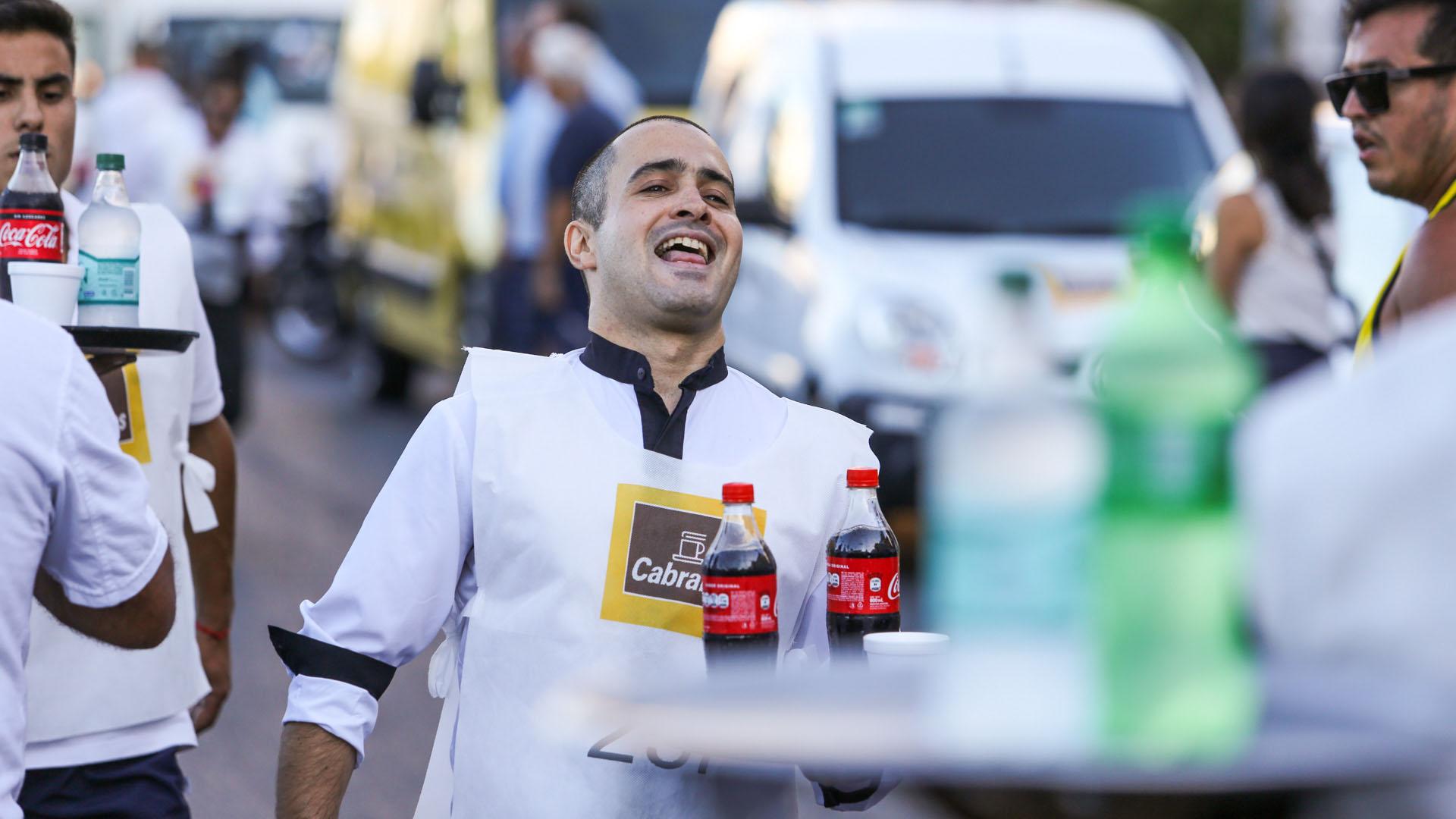 Uno de los competidores hace malabares para que no se le cayeran las botellas al apurar la caminata