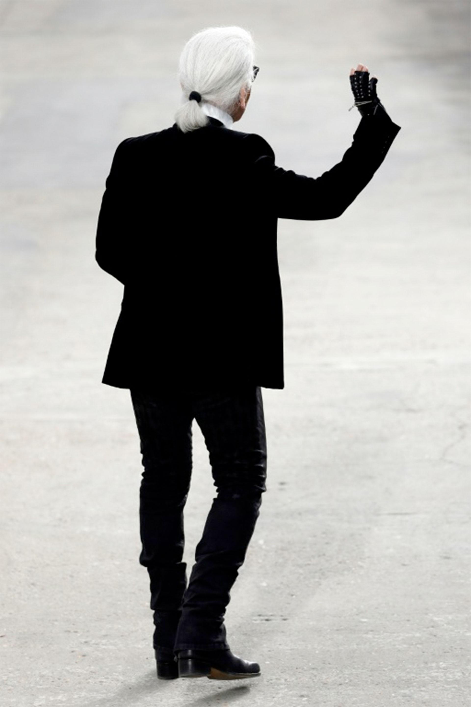 Karl Lagerfeld saluda al público tras un desfile de Chanel de prêt-à-porter primavera/verano 2014, el 1 de octubre de 2013 en París (AFP/Archivos – Patrick KOVARIK)