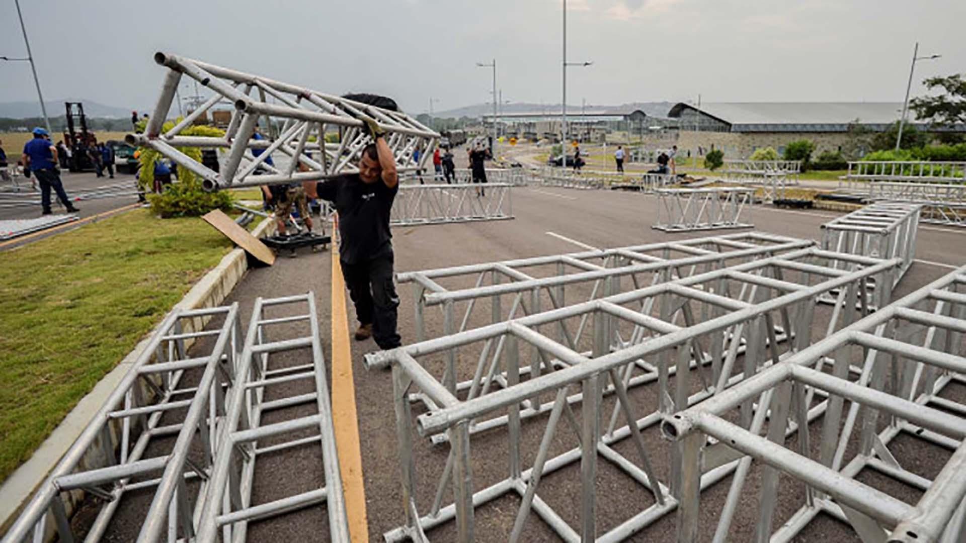 Decenas de trabajadores montan el escenario para el viernes 22 de febrero(Photo by Luis ROBAYO / AFP)