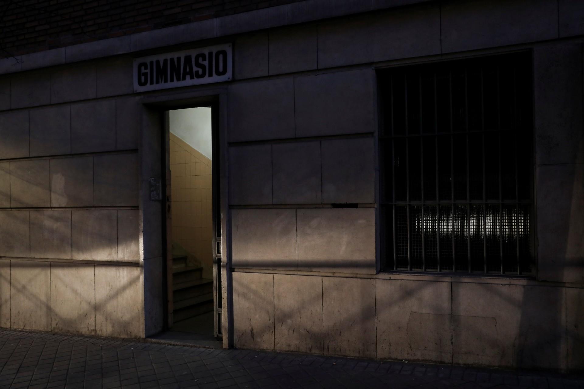 """Los faros de un automóvil que pasa en Madrid, España, el 14 de febrero de 2019, iluminan la entrada al gimnasio del colegio donde Fernando García-Salmones, de 58 años, dice que fue violado por un sacerdote hace casi 44 años. En una tarde lluviosa en 1975, García-Salmones estaba solo en el patio de recreo de su escuela cuando lo llamaron a la habitación de su abusador para que se secara. """"Se dio cuenta de que era vulnerable e indefenso, un pequeño ratón solitario"""", dijo. Cuando García-Salmones decidió llevar el caso a los tribunales en 1995, ya había ejecutado su estatuto de limitaciones."""