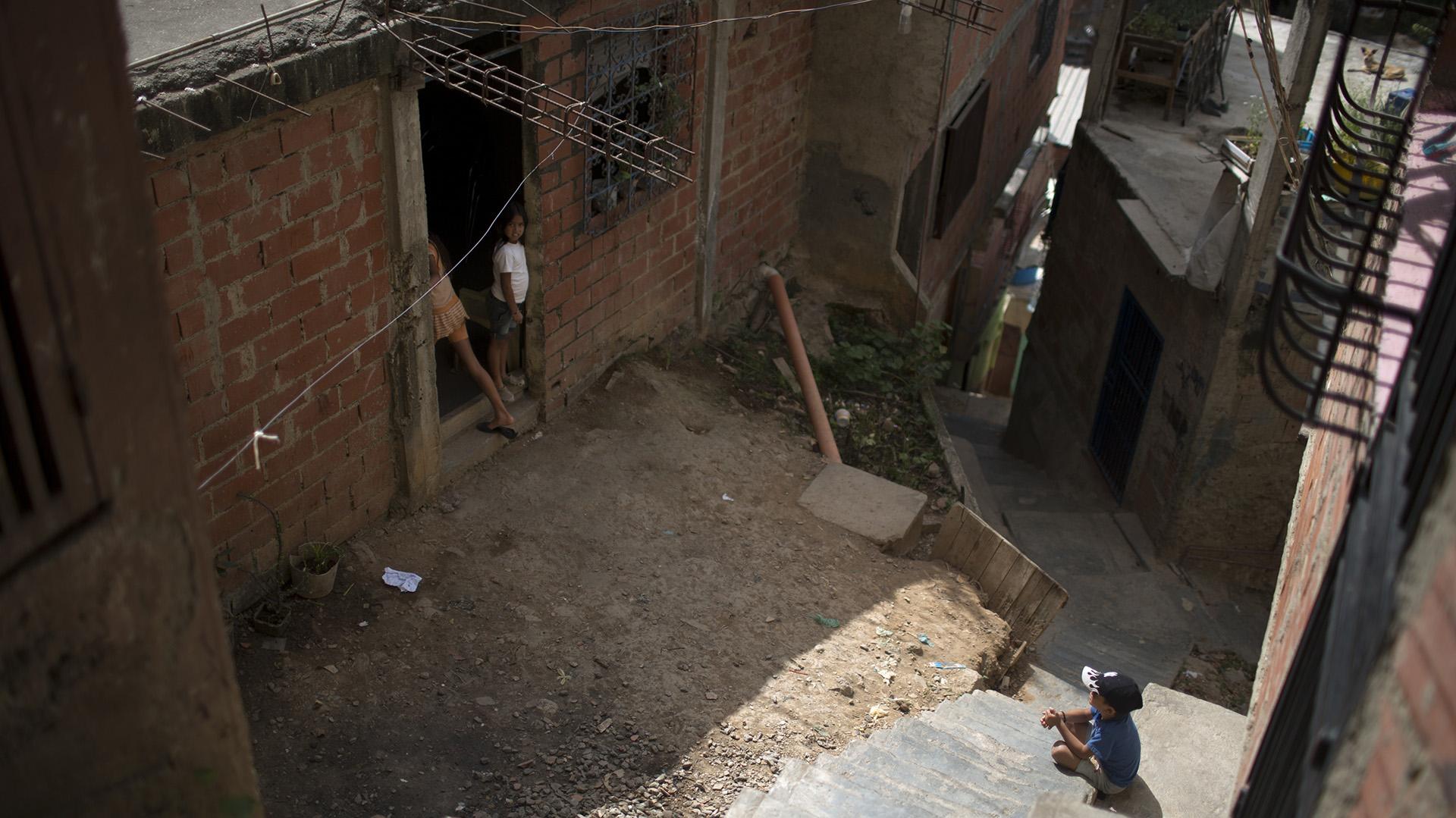 Niños se reúnen en la entrada de la que era la casa de Jhonny Godoy en La Vega, Caracas (AP/Ariana Cubillos)
