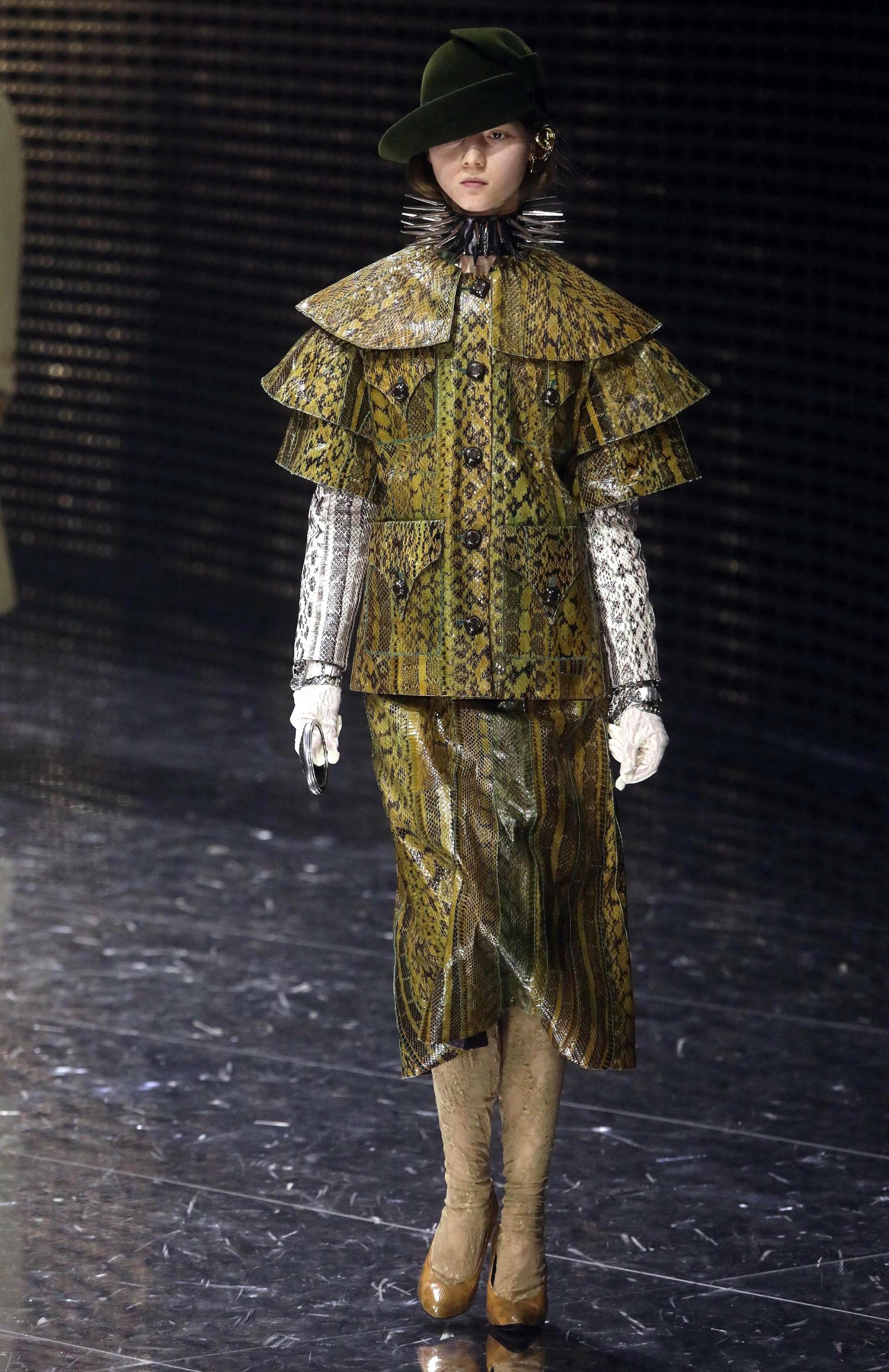 Total look de pitón. Un tailleur de saco con mangas en cascada y falda midi en color verde con mangas blancas y guantes blancos. Como accesorio, un choker de púas y sombrero de baby alpaca en color verde inglés