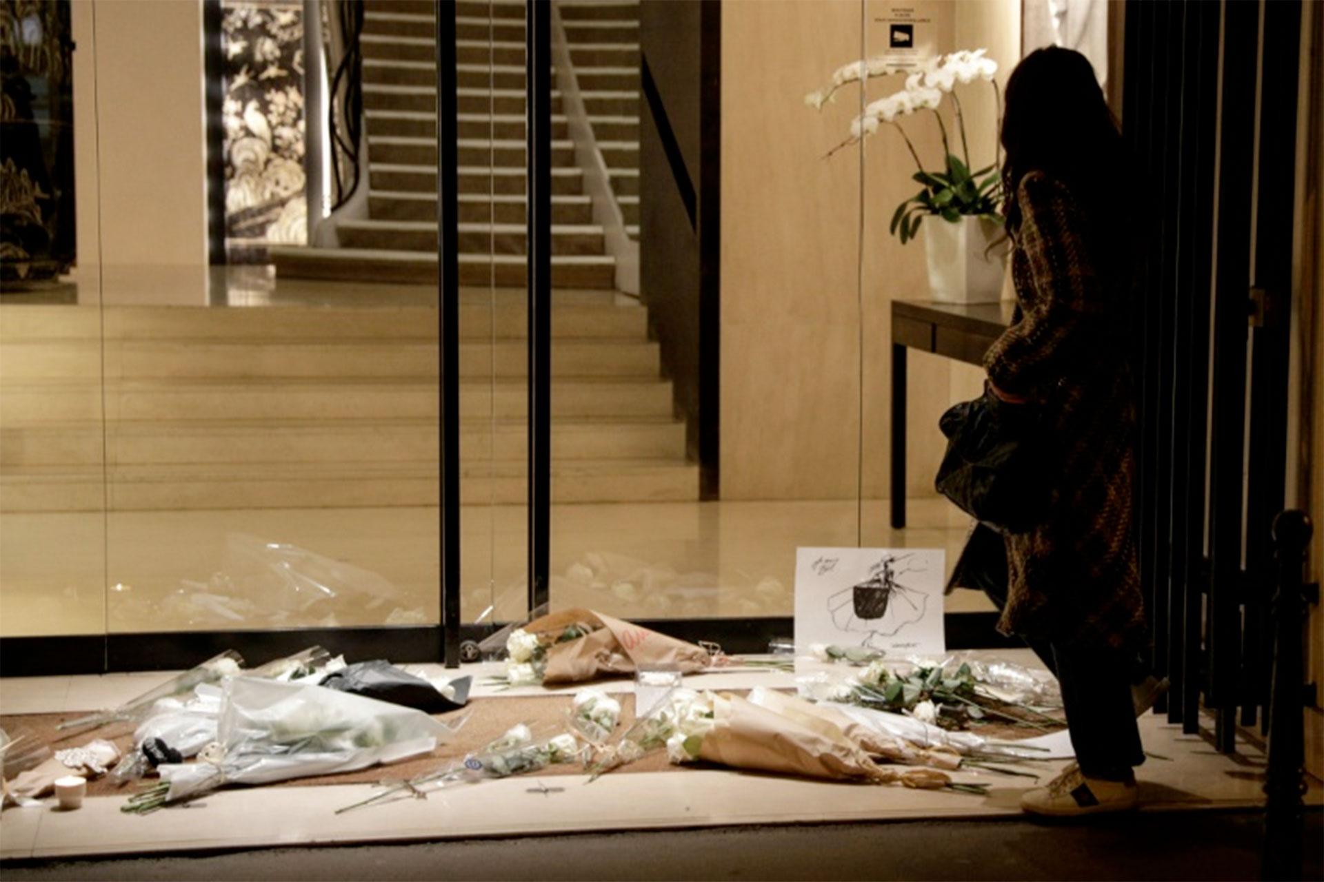 Una mujer permanece junto a un homenaje de flores al fallecido diseñador Karl Lagerfeld junto a la casa Chanel, en París, el 19 de febrero de 2019 (AFP – Geoffroy Van Der Hasselt)