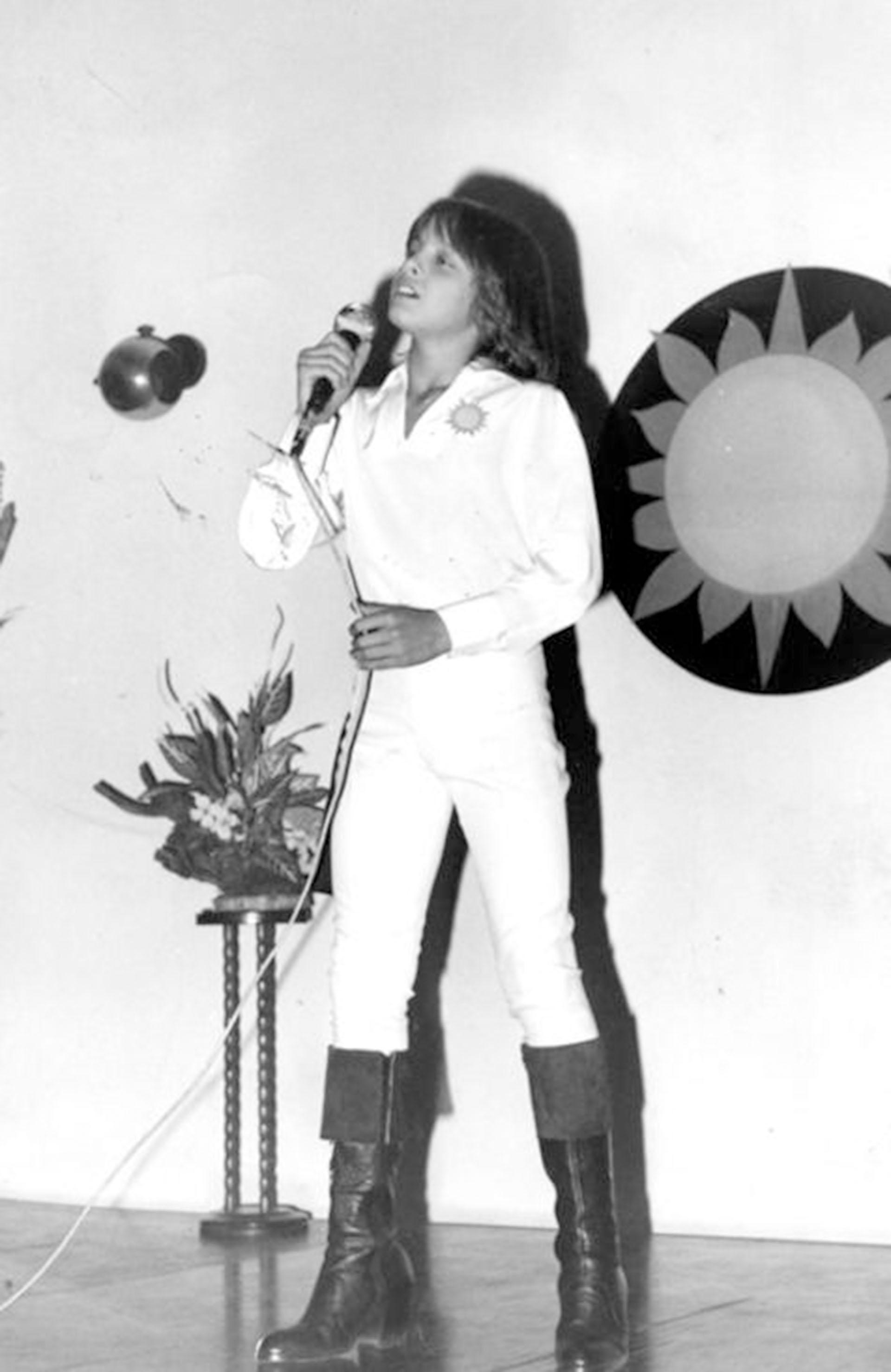Camisa de mangas largas con un sol bordado, pantalones achupinados, botas de caña alta, un sello durante su niñez