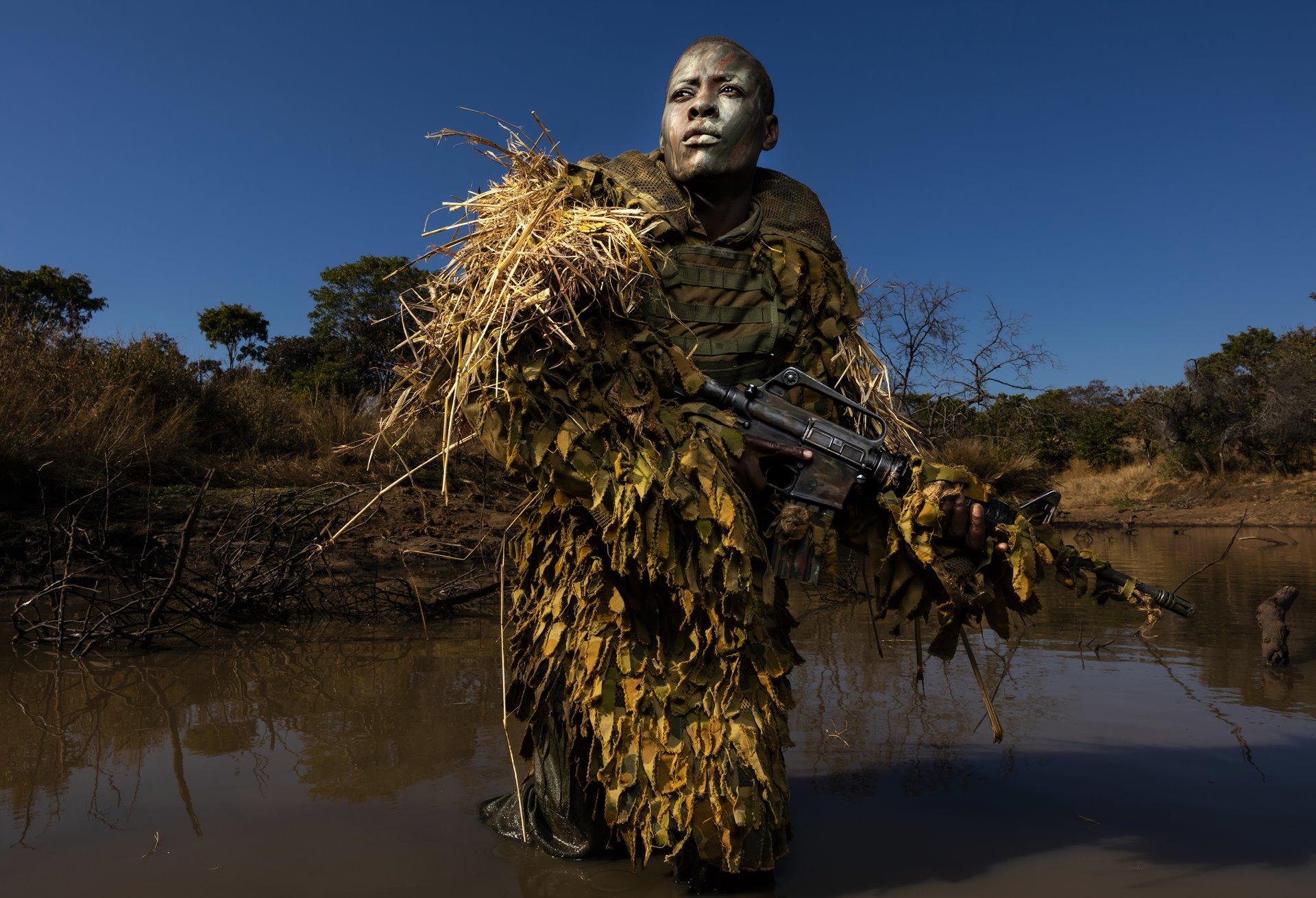 Petronella Chigumbura (30), miembro de una unidad femenina contra la caza furtiva llamada Akashinga, participa en un entrenamiento de ocultación en el Parque de Vida Silvestre de Phundundu, Zimbabwe / Foto: Brent Stirton (Getty Images)