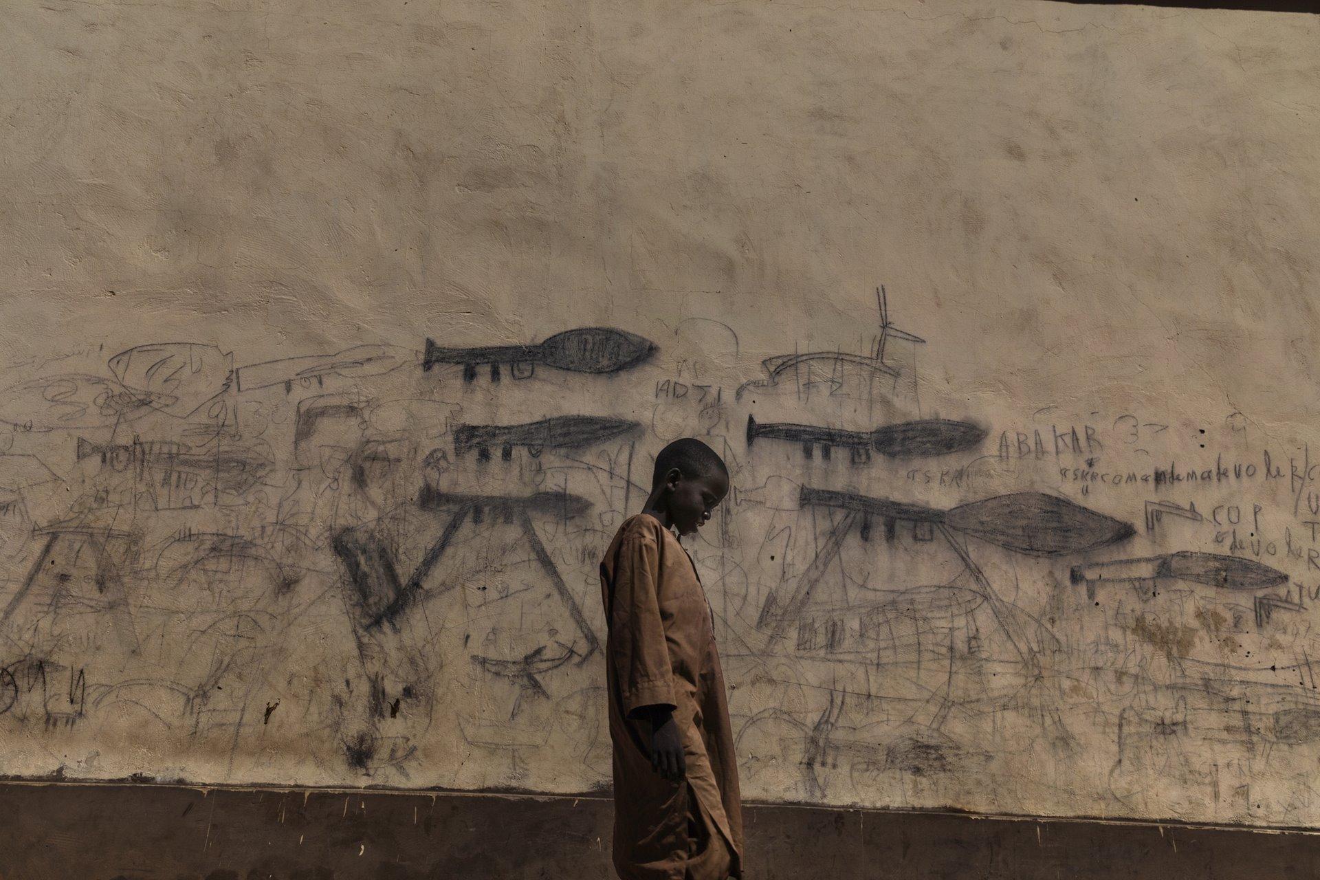 Un niño huérfano pasea junto a una pared con dibujos que muestran lanzadores de granadas propulsados por cohetes en Bol, Chad / Foto: Marco Gualazzini (Contrasto Online)