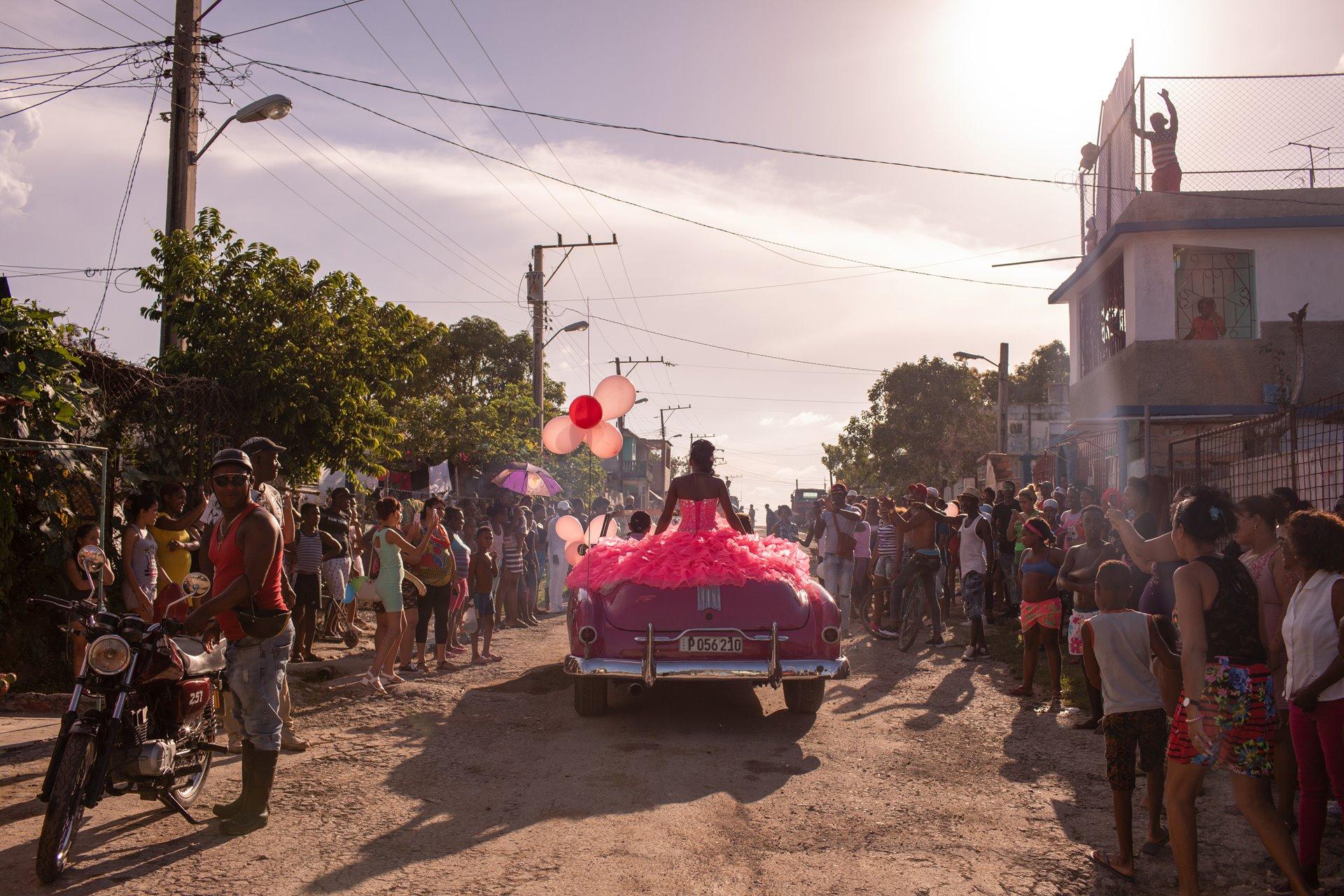Pura recorre su vecindario en un convertible rosado de la década de 1950, mientras la comunidad se reúne para celebrar su decimoquinto cumpleaños en La Habana, Cuba / Foto: Diana Markosian (Magnum Photos)