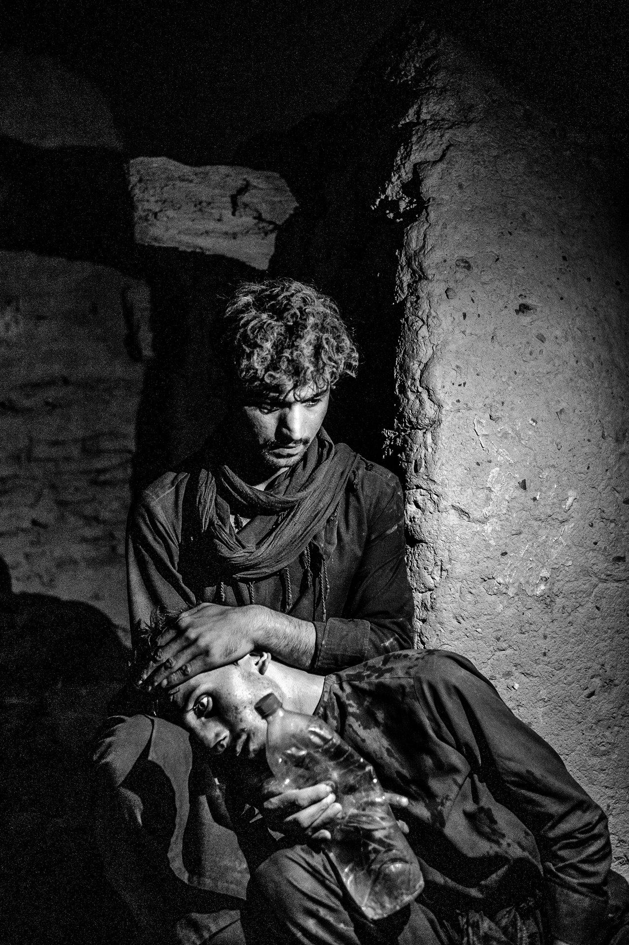 Un refugiado afgano consuela a su compañero mientras espera el transporte a través de la frontera oriental de Irán, el 27 de julio. ACNUR informa que Irán tiene casi un millón de refugiados registrados, la gran mayoría de Afganistán / Foto: Enayat Asadi