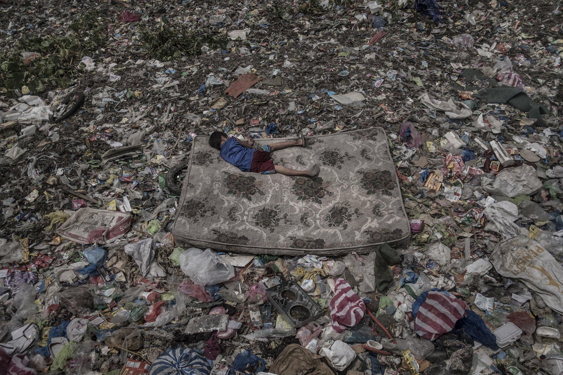 Un niño que recolecta material reciclable yace en un colchón rodeado de basura flotando en el río Pasig, en Manila, Filipinas. El río Pasig fue declarado biológicamente muerto en la década de 1990, debido a una combinación de contaminación industrial y desechos que son arrojados por comunidades cercanas que viven sin la infraestructura de saneamiento adecuada / Foto: Mário Cruz