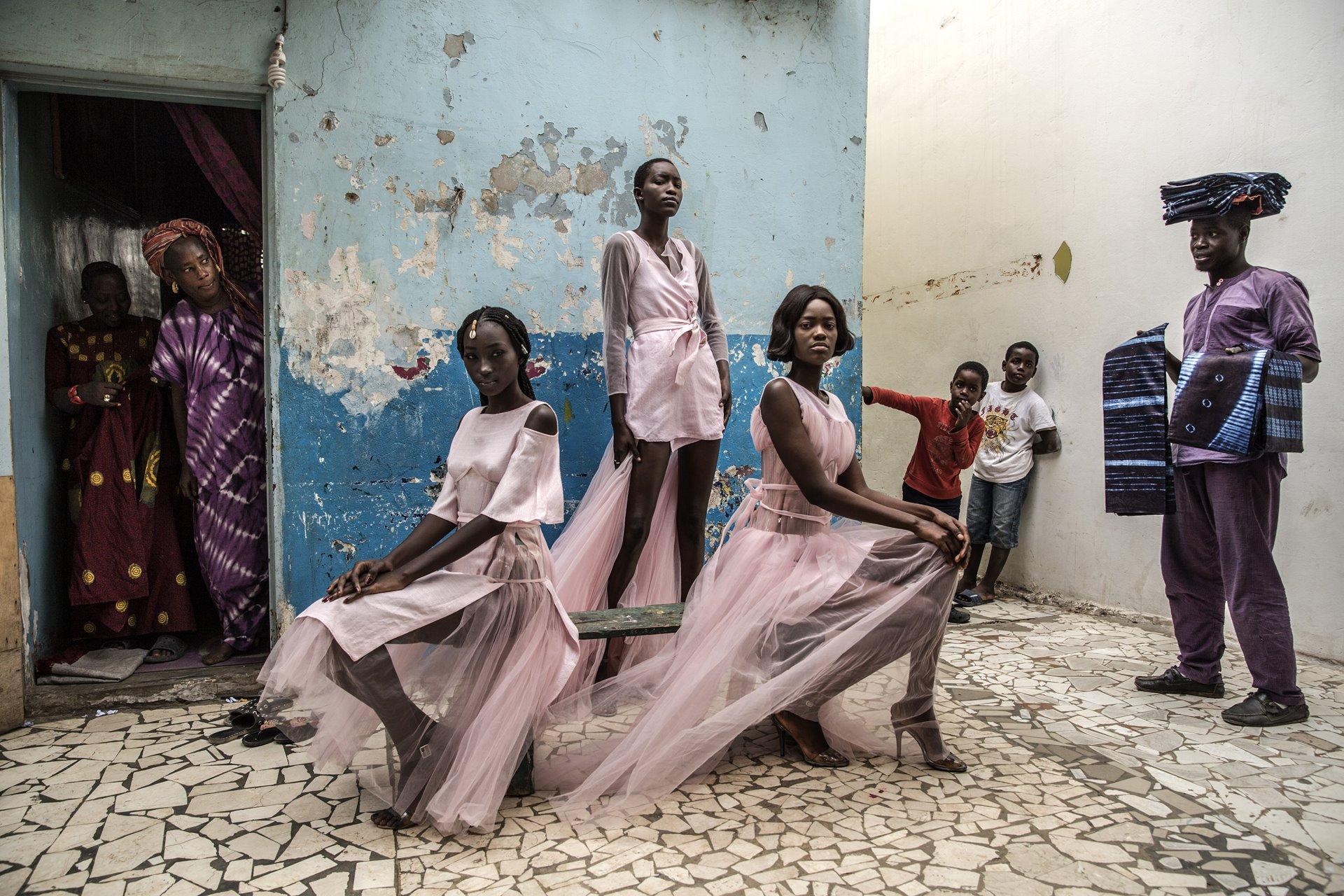 Diarra Ndiaye, Ndeye Fatou Mbaye y Malezi Sakho modelan los atuendos del diseñador Adama Paris, en el barrio de Medina en la capital senegalesa de Dakar, mientras los curiosos residentes observan. Dakar es un centro creciente de la moda franco-africana, y es el hogar de Fashion Africa TV, la primera cadena de televisión dedicada por completo a la moda en el continente / Foto: Finbarr O'Reilly