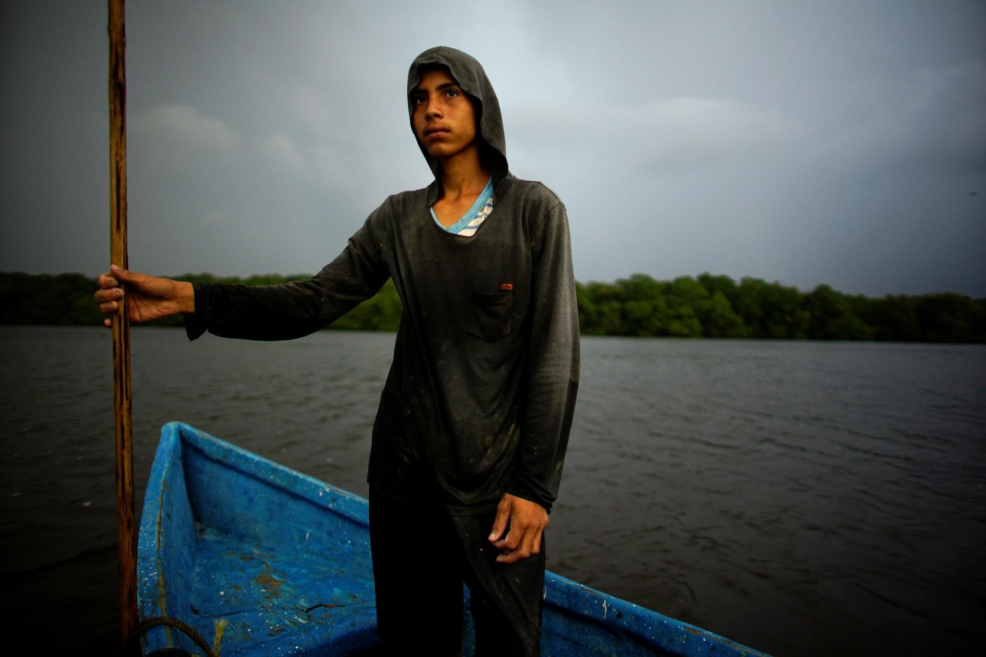 El pescador Luis Angel Gimenez, de 14 años, se para en su bote en la laguna de Mecoacan cerca de Paraiso, México, el 9 de diciembre de 2018.