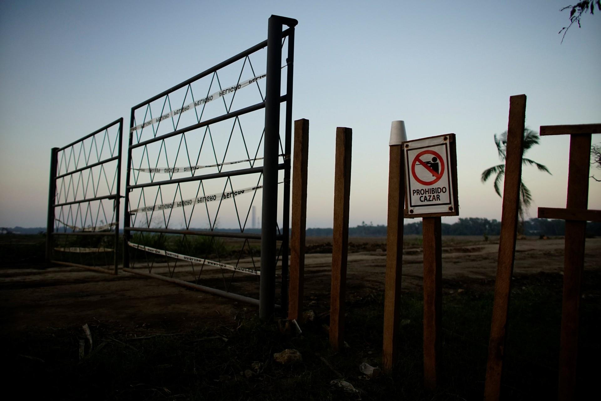 """Un cartel que dice """"Prohibido cazar"""" en español, se encuentra en la entrada de un área que pertenece a la compañía petrolera estatal Pemex, en la cual se planea construir una nueva refinería de petróleo en Paraiso, México, el 8 de diciembre de 2018."""