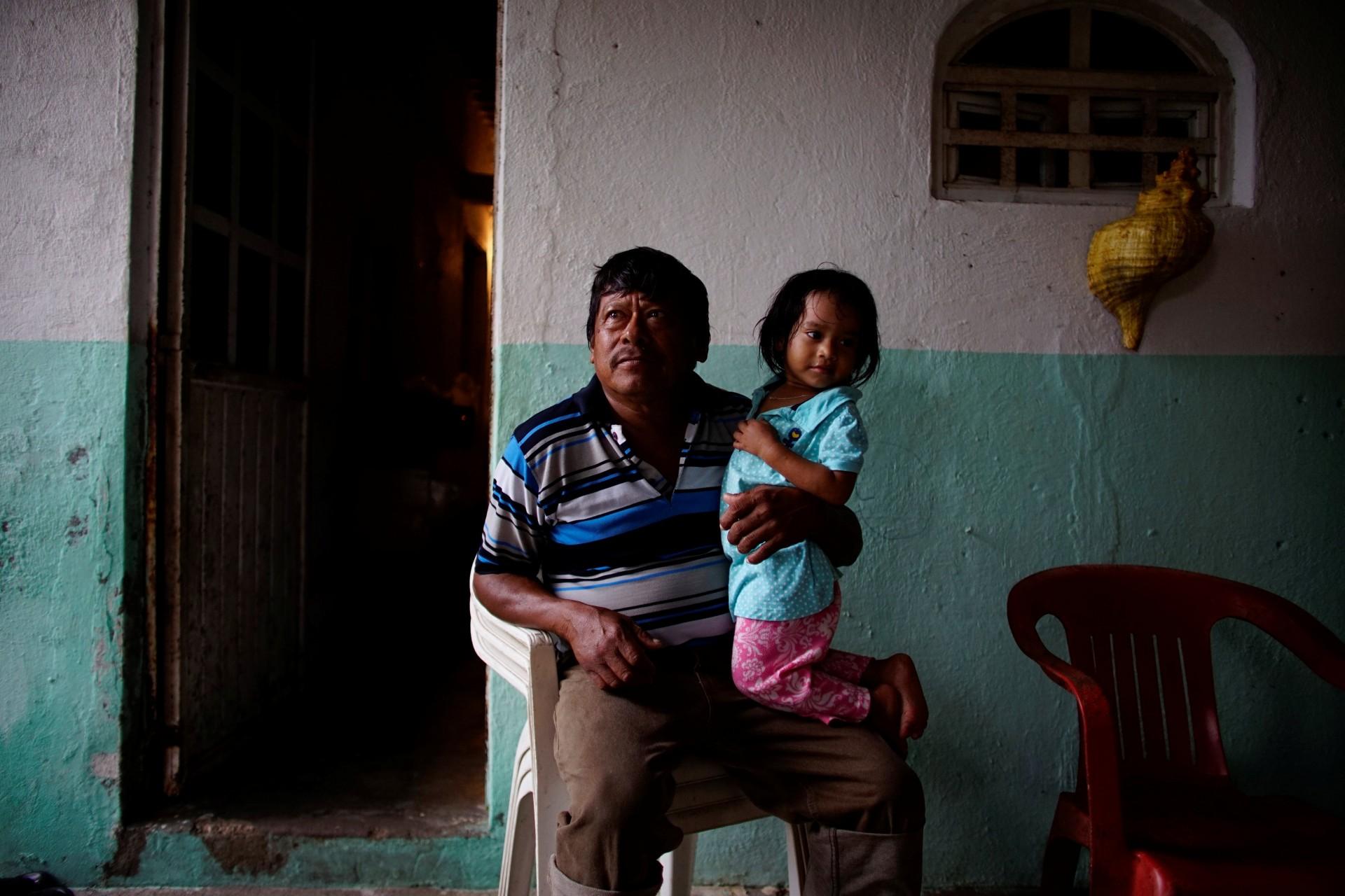 El pescador Rafael de la Cruz Hernández, de 60 años, tiene a su nieta de dos años en el pueblo de Chiltepec, en Paraiso, México, el 9 de diciembre de 2018.