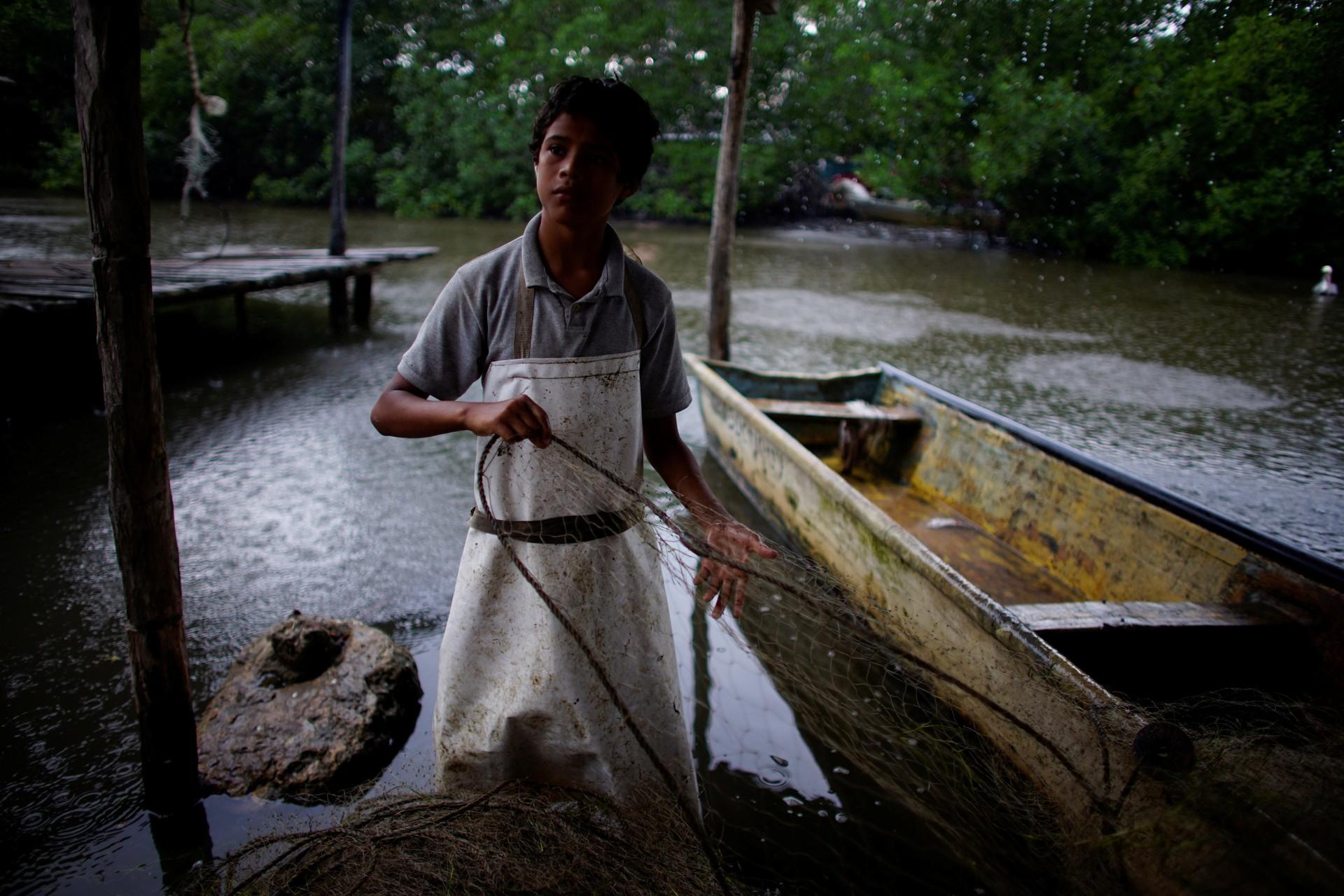 Alexander Giménez, de 13 años, revisa una red de pesca en el pueblo de Chiltepec, en Paraiso, México, el 9 de diciembre de 2018.