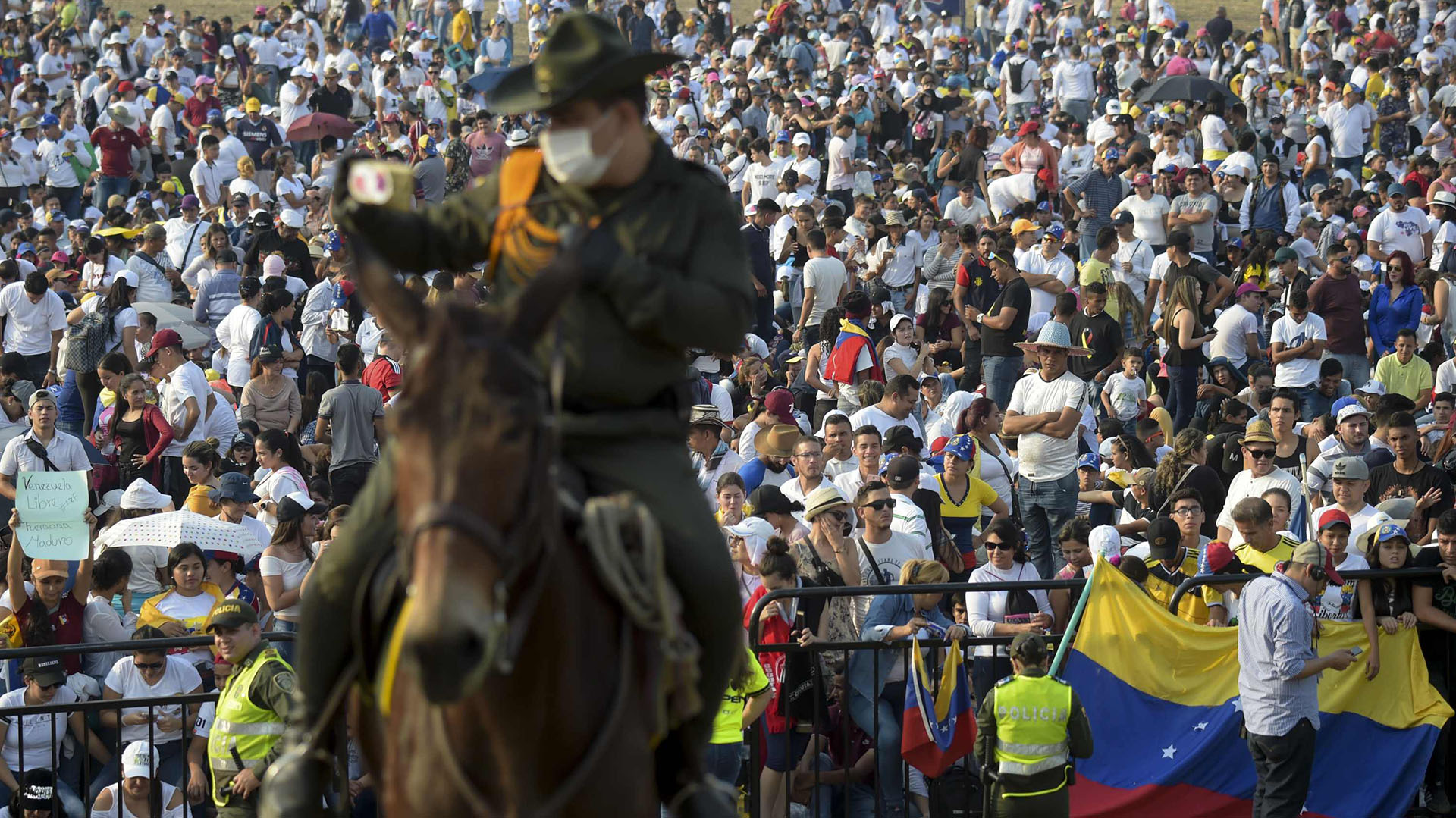 """Un policía a caballo en guardia mientras la gente espera el comienzo del concierto """"Venezuela Aid Live"""", organizado por el multimillonario británico Richard Branson para recaudar fondos para la ayuda humanitaria a Venezuela en el Puente Internacional Tienditas en Cúcuta, Colombia, el 22 de febrero de 2019. (AFP)"""