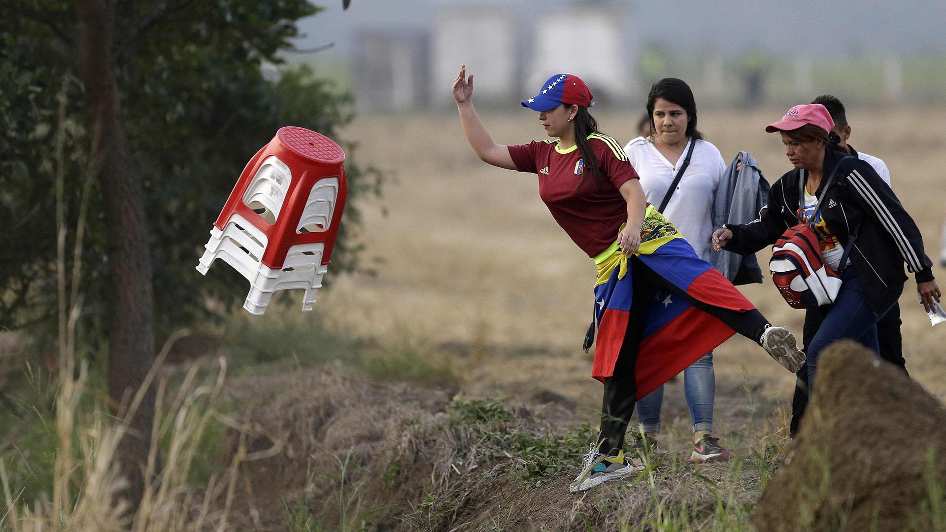 Una mujer venezolana agarra un juego de taburetes de plástico cuando llega para el concierto de Venezuela Aid Live en el lado colombiano del Puente Internacional Tienditas en las afueras de Cúcuta, Colombia, el viernes 22 de febrero de 2019, en la frontera con Venezuela. (AP)