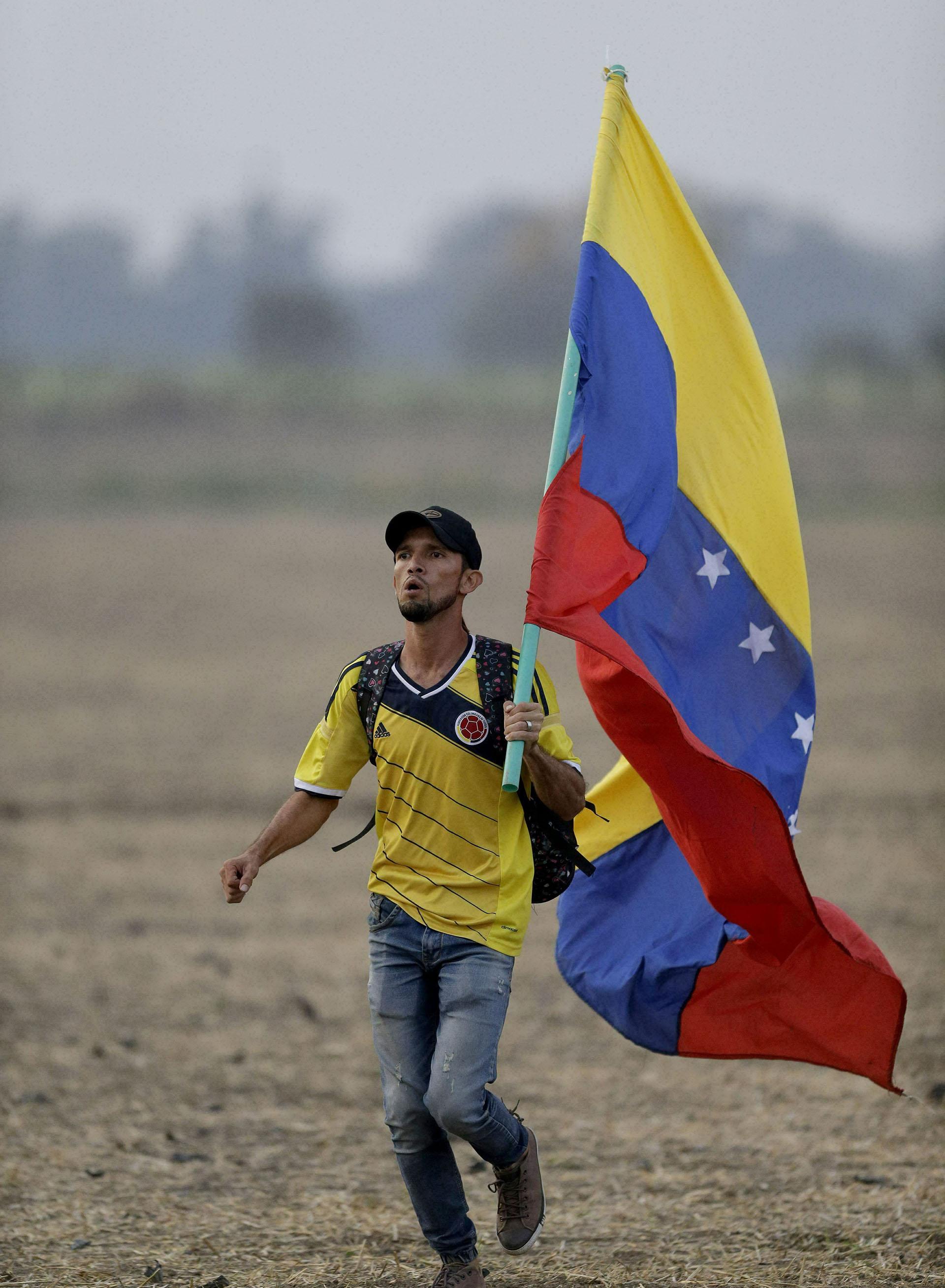 Un hombre con una bandera venezolana corre al llegar al concierto de Venezuela Aid Live. (AP)
