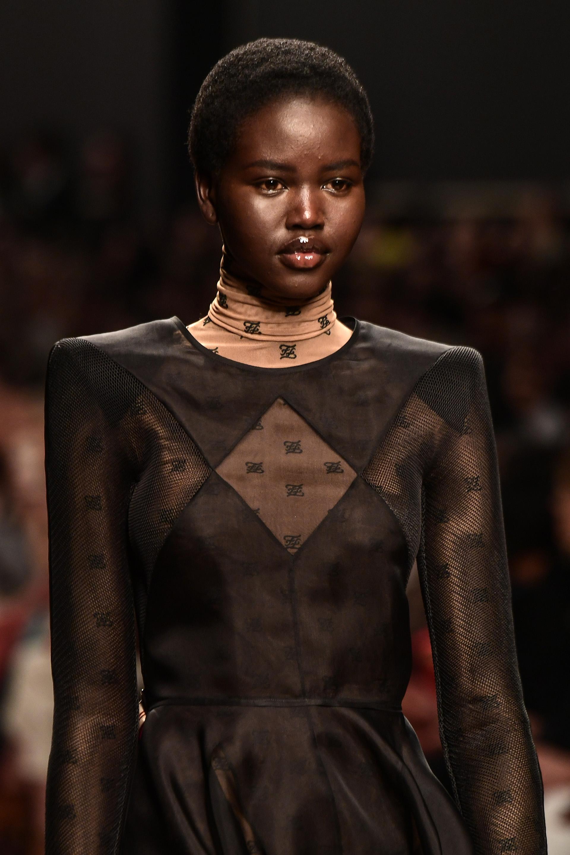 Adut Akech lució un little black dresscon sello Fendi. Catsuit polera debajo y por encima un vestidito negro con mangas de red. Una última versión del LBD de Lagerfeld