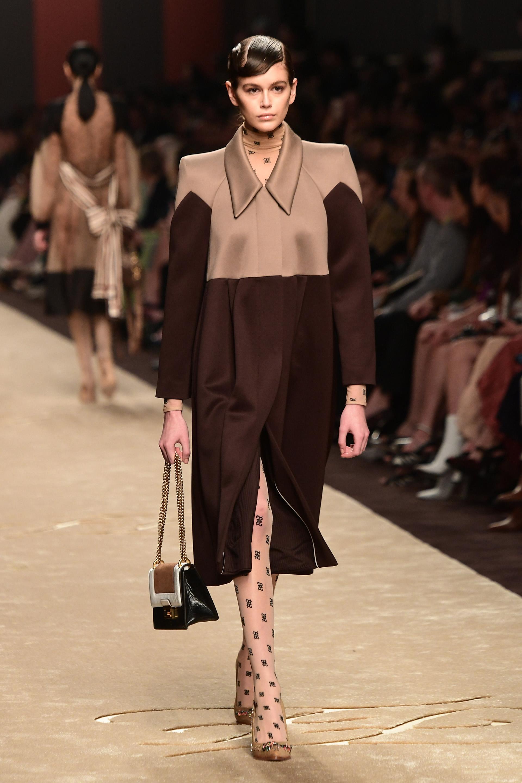 Kaia Gerber, otra musa de Lagerfeld, desfiló con sobretodo bicolor beige y chocolate. Stilettos de pcv con piedras preciosas y un clásico bolso de Fendi