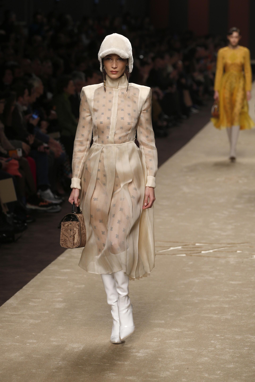 La top model Bella Hadid también se hizo presente en la pasarela de Fendi. Lució un vestido de organza en beige plisado con corte en la cintura, hombreras y cuello polera. El look se completó con bucaneras a la rodilla en cuero blanco y casquete de piel con visera. Como accesorio, un bolso tramado en ocre