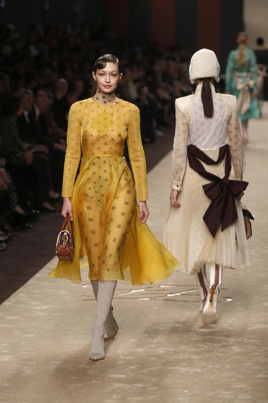 Gigi Hadid fue una de las encargadas de cerrar el desfile de Fendi, el último show que tuvo un gran homenaje a Karl. La top model lució un diseño en organza amarillo a la rodilla. Debajo un catsuit de cuello polera con las nuevas siglas de Fendi diseñadas por Lagerfeld y mini bag