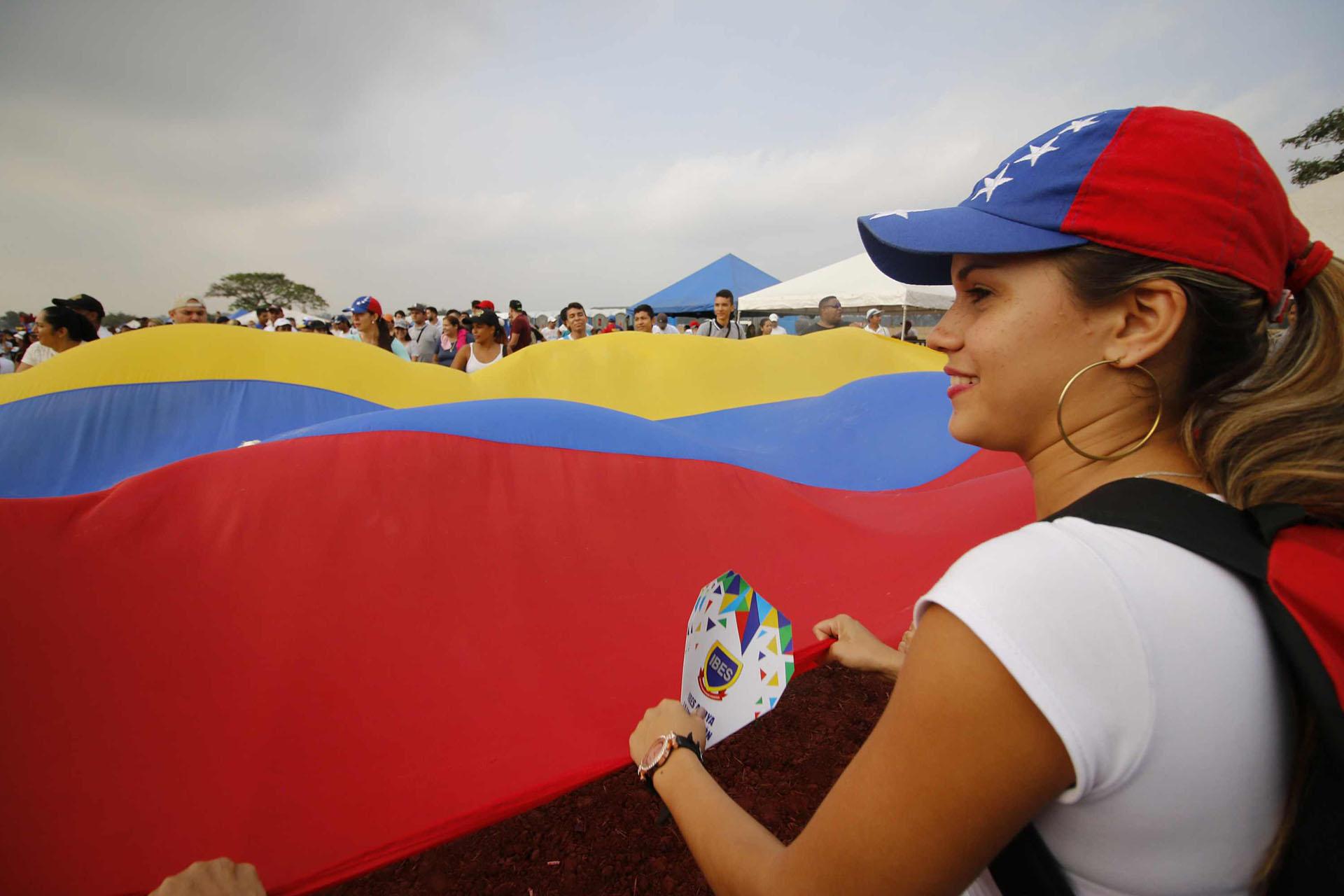 """Una gran bandera de Venezuela se desplegó entre la multitud en el concierto """"Venezuela Aid Live"""". (AFP)"""