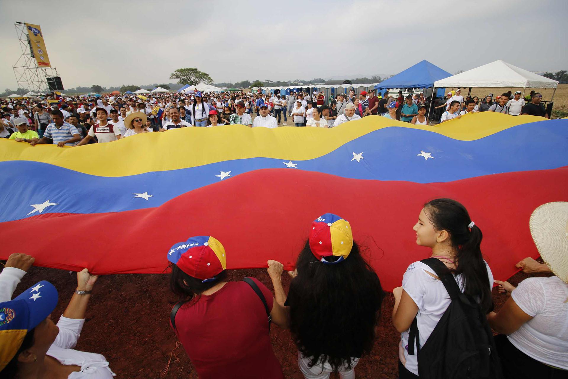 """Decenas de venezolanos sostienen una gran bandera de su país en el concierto """"Venezuela Aid Live"""". (AFP)"""
