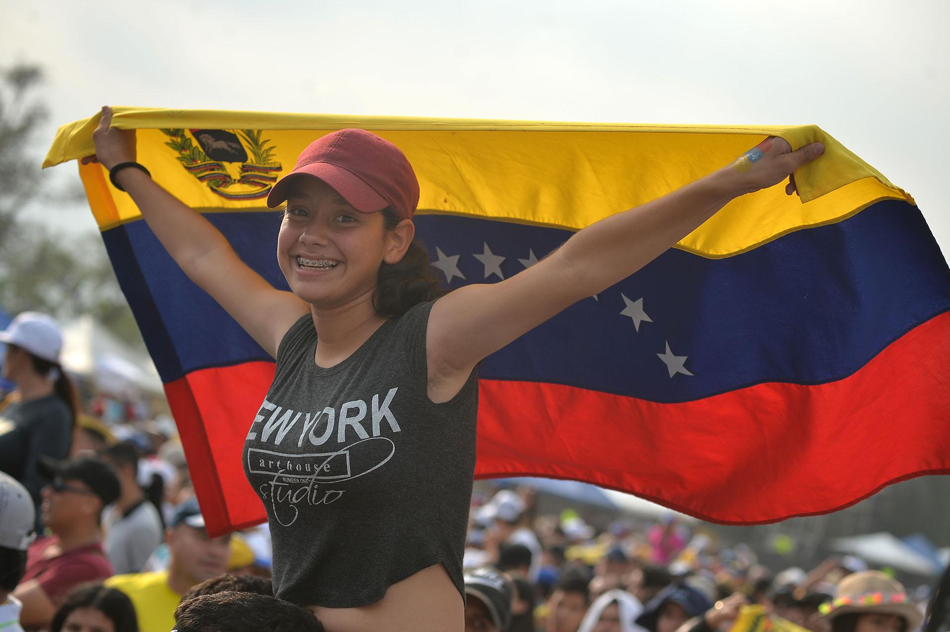 """Una mujer sostiene una bandera de Venezuela sobre los hombros de un compañero en el concierto """"Venezuela Aid Live"""". (AFP)"""