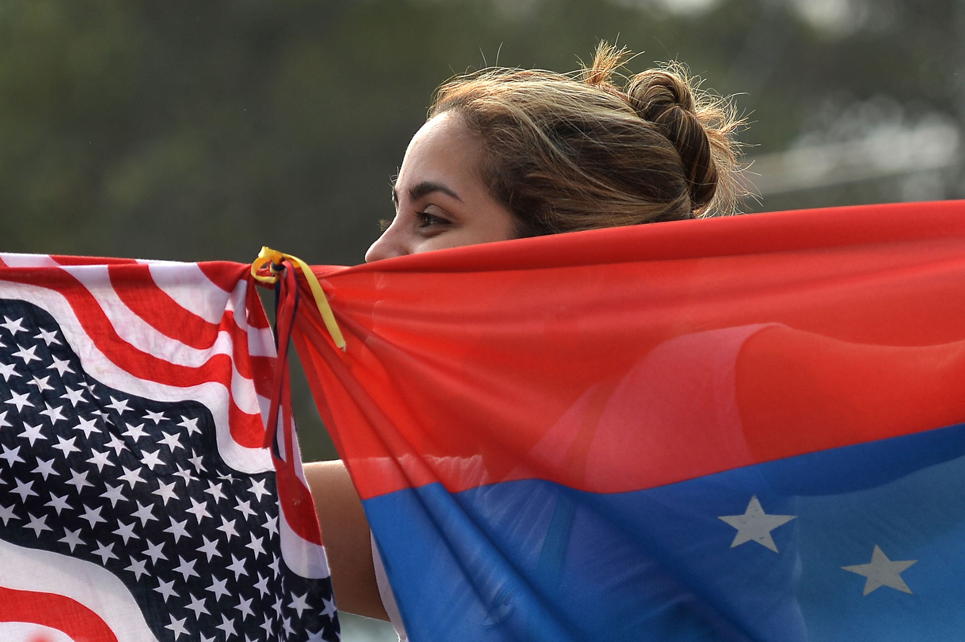 Una mujer junta las banderas de Venezuela y los Estados Unidos.