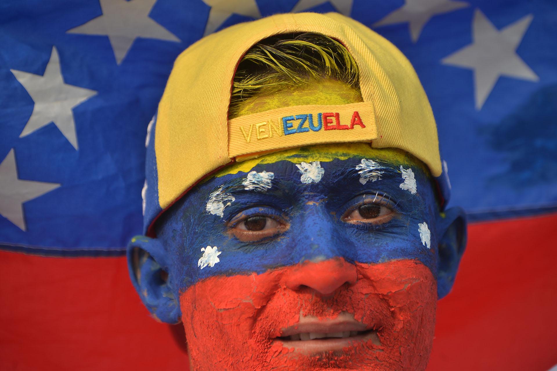 """Un hombre con la cara pintada en los colores de la bandera de Venezuela en el concierto """"Venezuela Aid Live"""". (AFP)"""