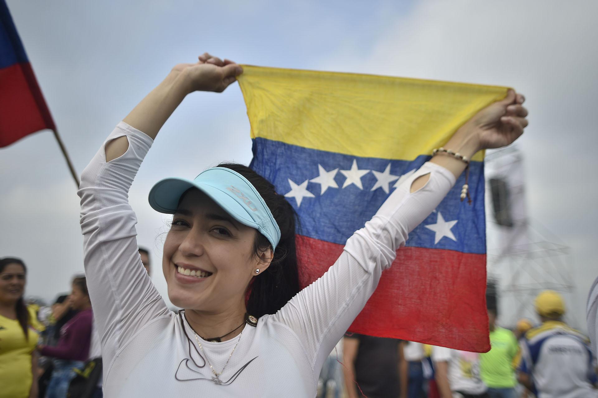 Una mujer alza una bandera de Venezuela. (AFP)