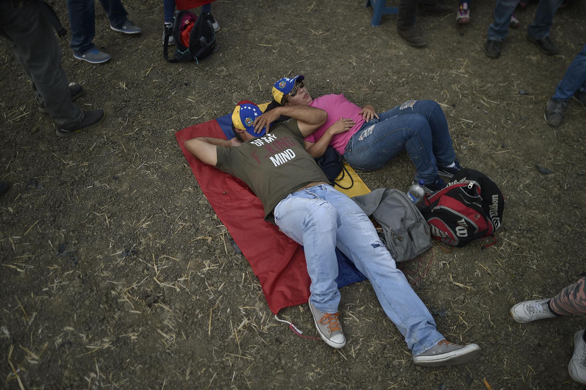 """Una pareja descansa mientras espera el comienzo del concierto """"Venezuela Aid Live"""". (AFP)"""