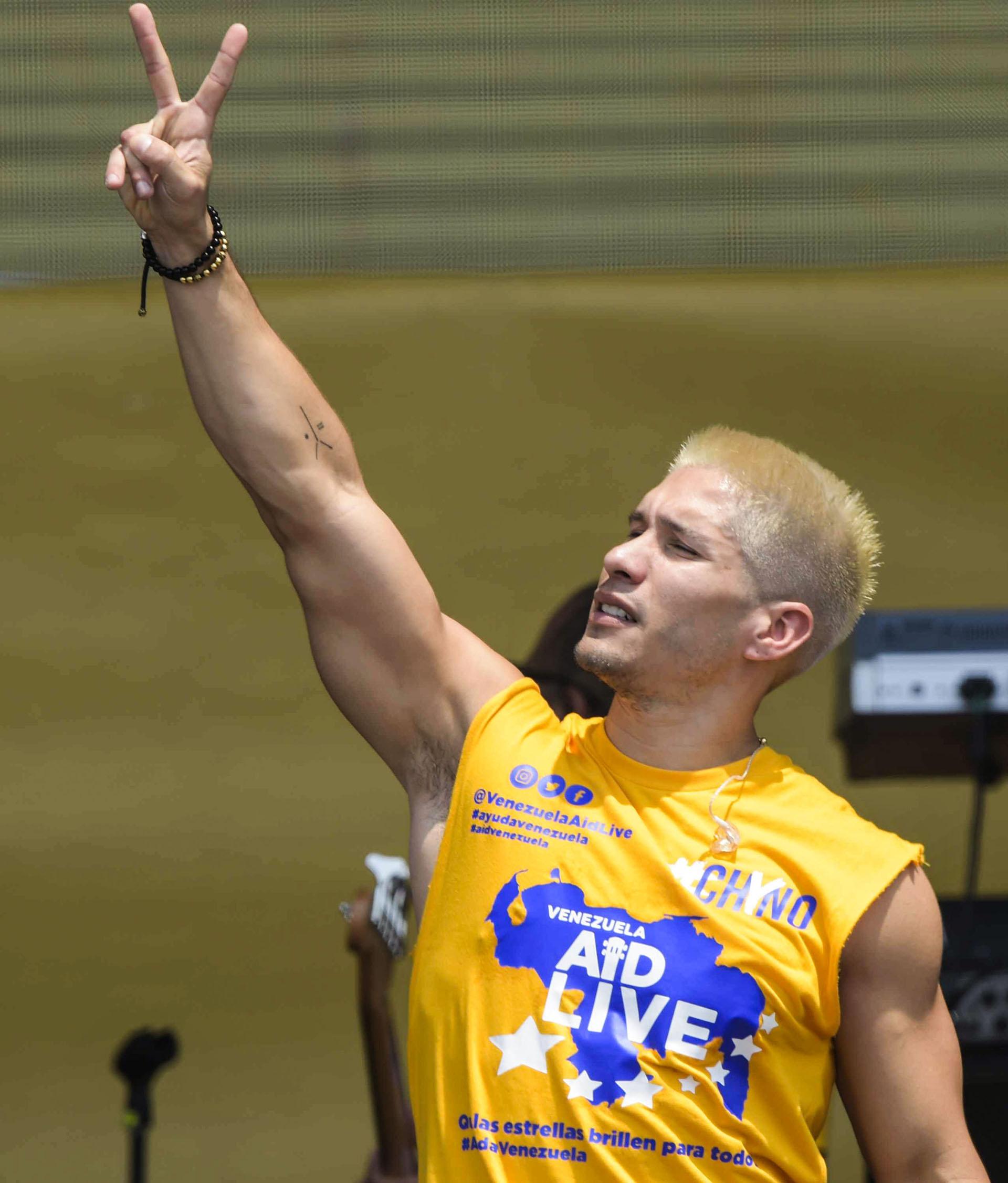 """El cantante venezolano """"Chyno"""" forma la letra V durante su actuación en el concierto """"Venezuela Aid Live"""". (AFP)"""