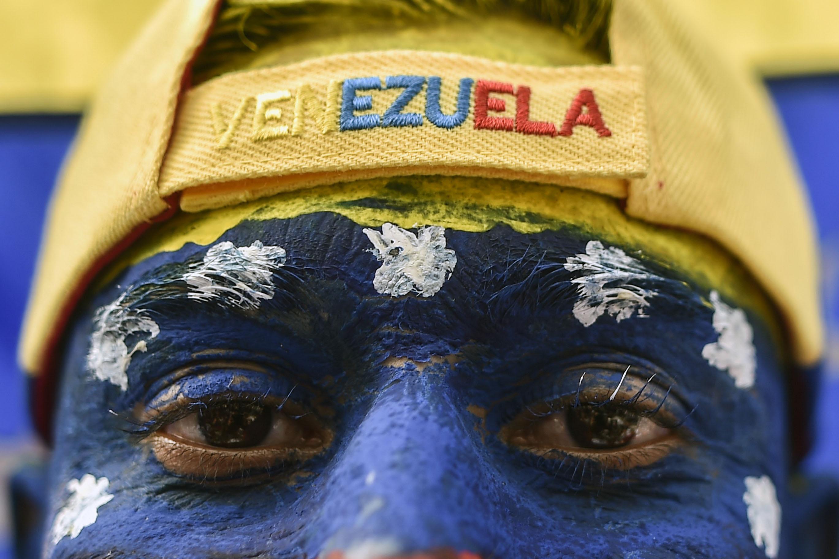 """Un hombre con la cara pintada con los colores nacionales de Venezuela, asiste al concierto """"Venezuela Aid Live"""" en el Puente Internacional Tienditas en Cúcuta, Colombia, el 22 de febrero de 2019. (AFP)"""