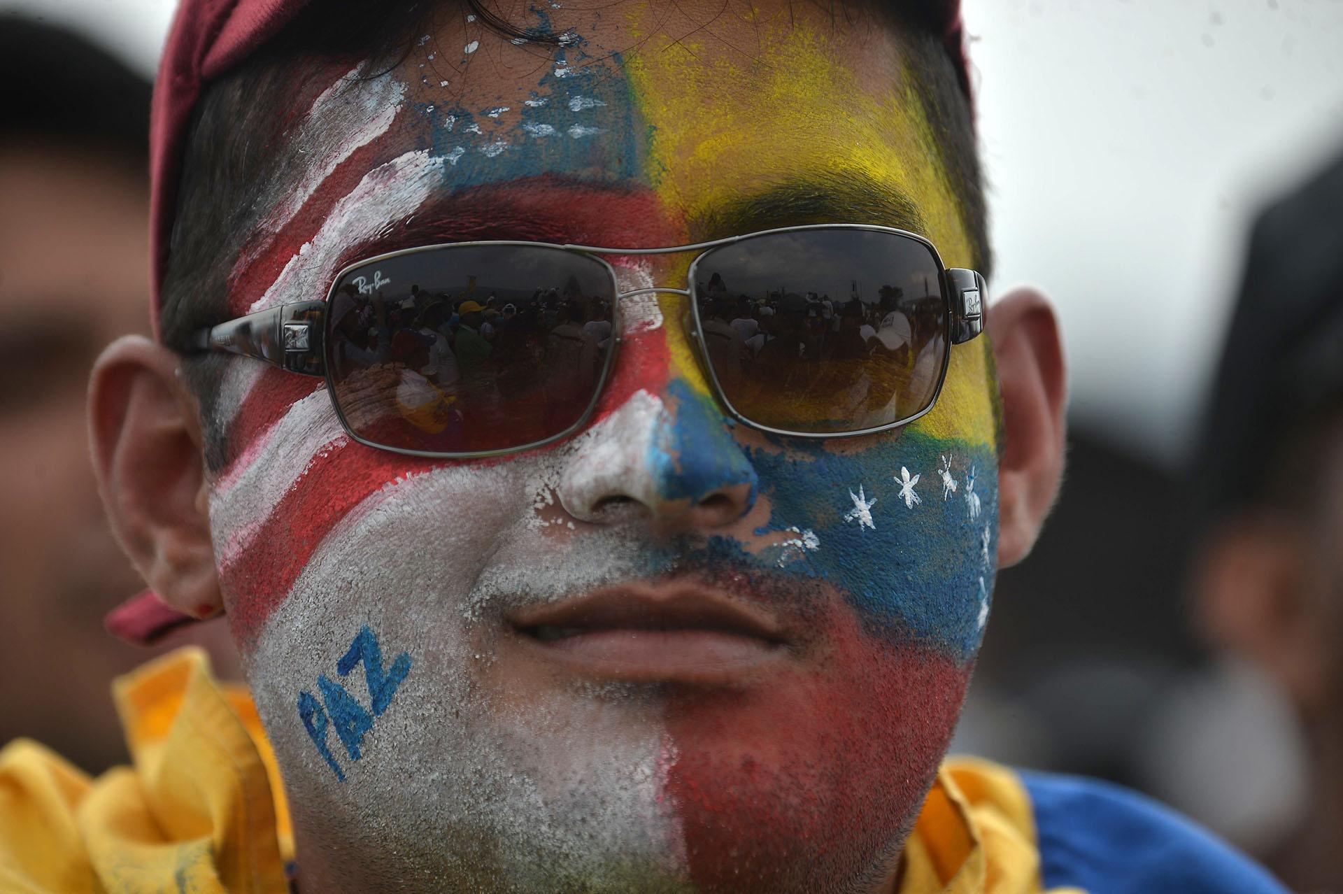 Un hombre con la cara pintada con las banderas de Venezuela y Estados Unidos. (AFP)
