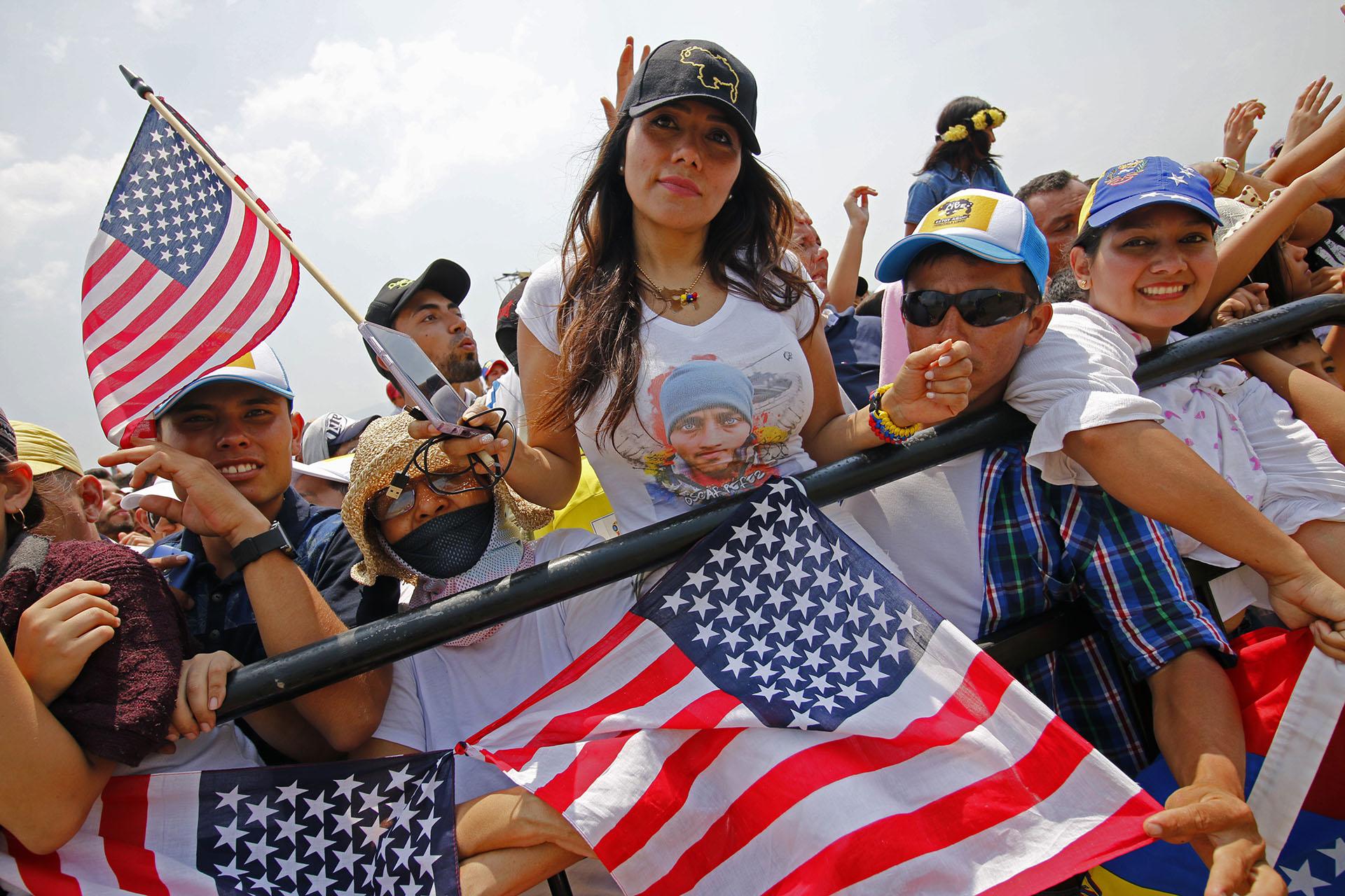 """Una mujer sostiene una bandera estadounidense mientras participa en el concierto """"Venezuela Aid Live"""". (AFP)"""