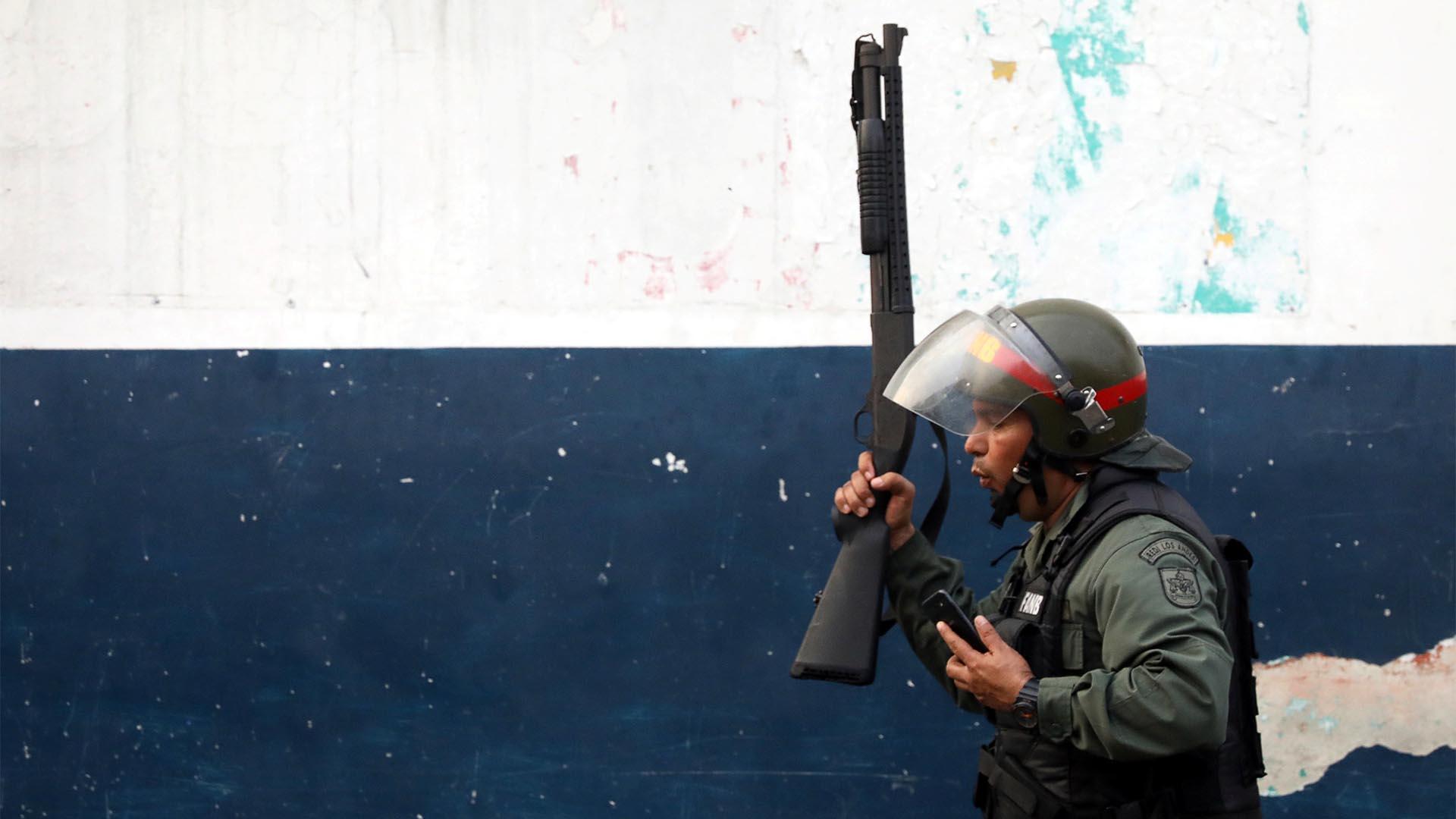 Un miembro de las fuerzas de seguridad de Venezuela camina en la ciudad fronteriza de Ureña. Las fuerzas de seguridad chavistas intentan frenar a la multitud que busca ayuda humanitaria (Reuters)