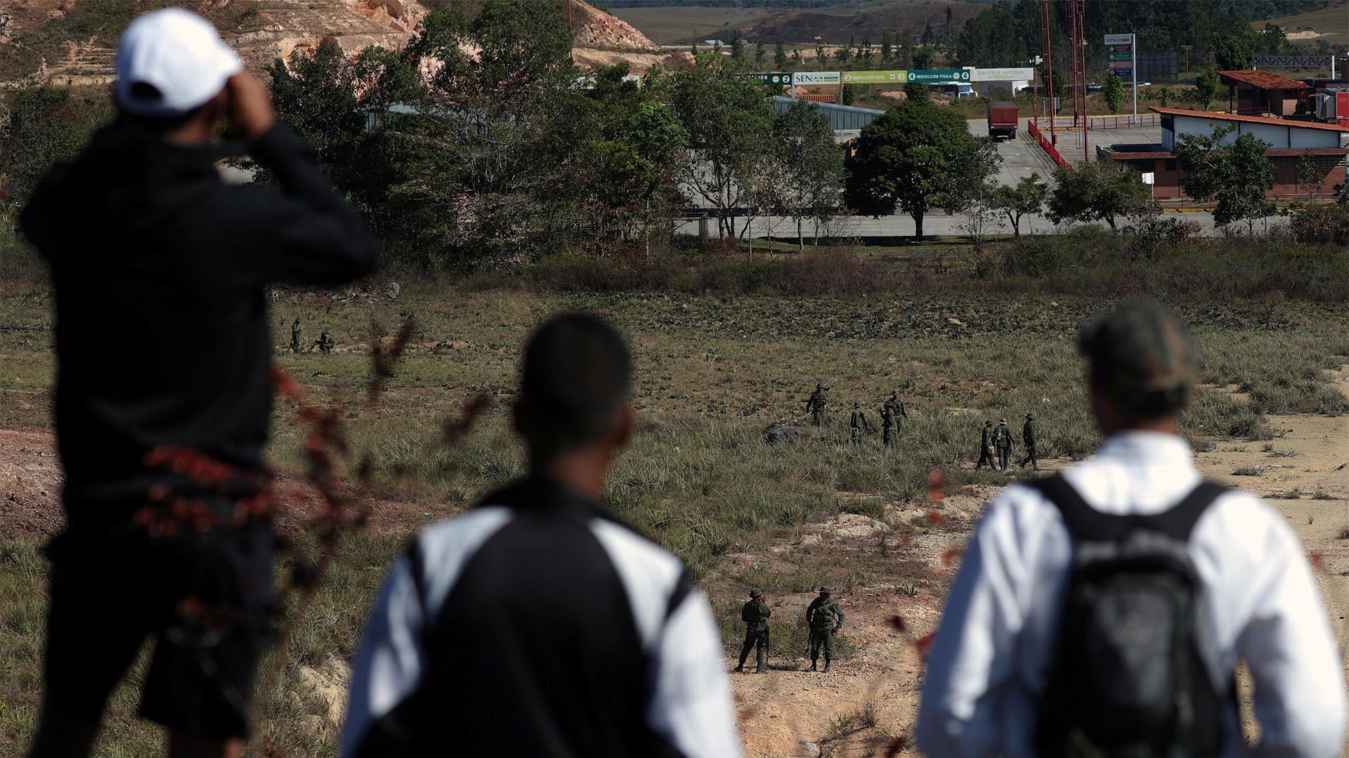 Hombres observan a los soldados venezolanos que vigilan la frontera entre Venezuela y Brasil en Pacaraima, estado de Roraima (Reuters)