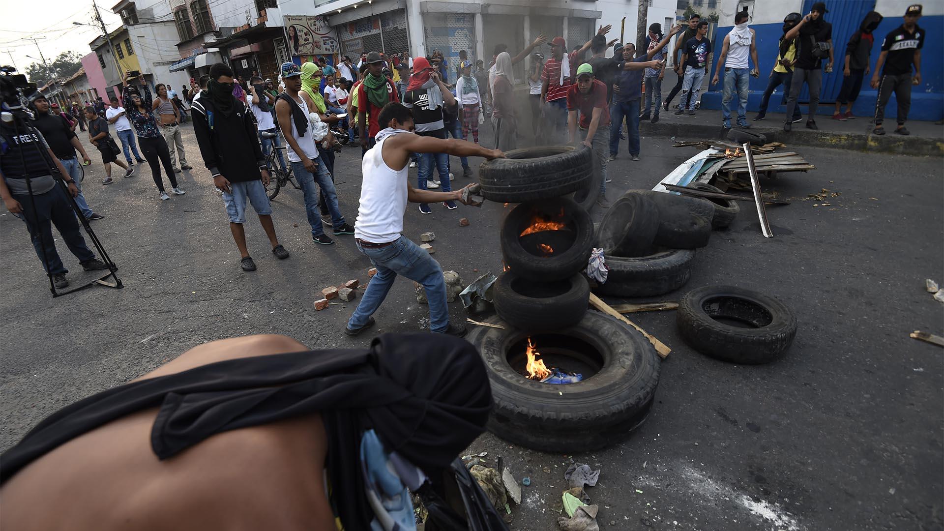 Los venezolanos se enfrentan a guardias nacionales en la ciudad fronteriza de Ureña luego de que el gobierno de Maduro ordenara cerrar temporalmente la frontera con Colombia (AFP)