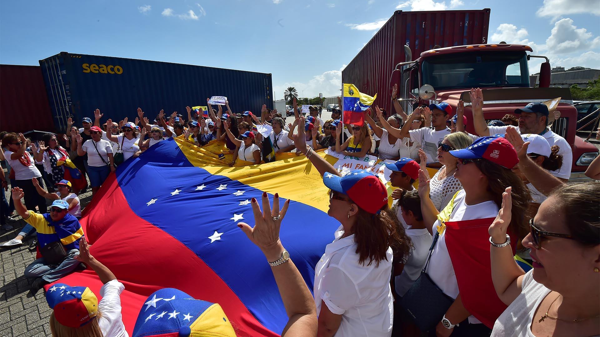 Los simpatizantes del líder opositor venezolano, Juan Guaidó, sostienen banderas y señales que respaldan la ayuda humanitaria en el puerto de Willemstad, Curazao, Antillas Holandesas (AFP)