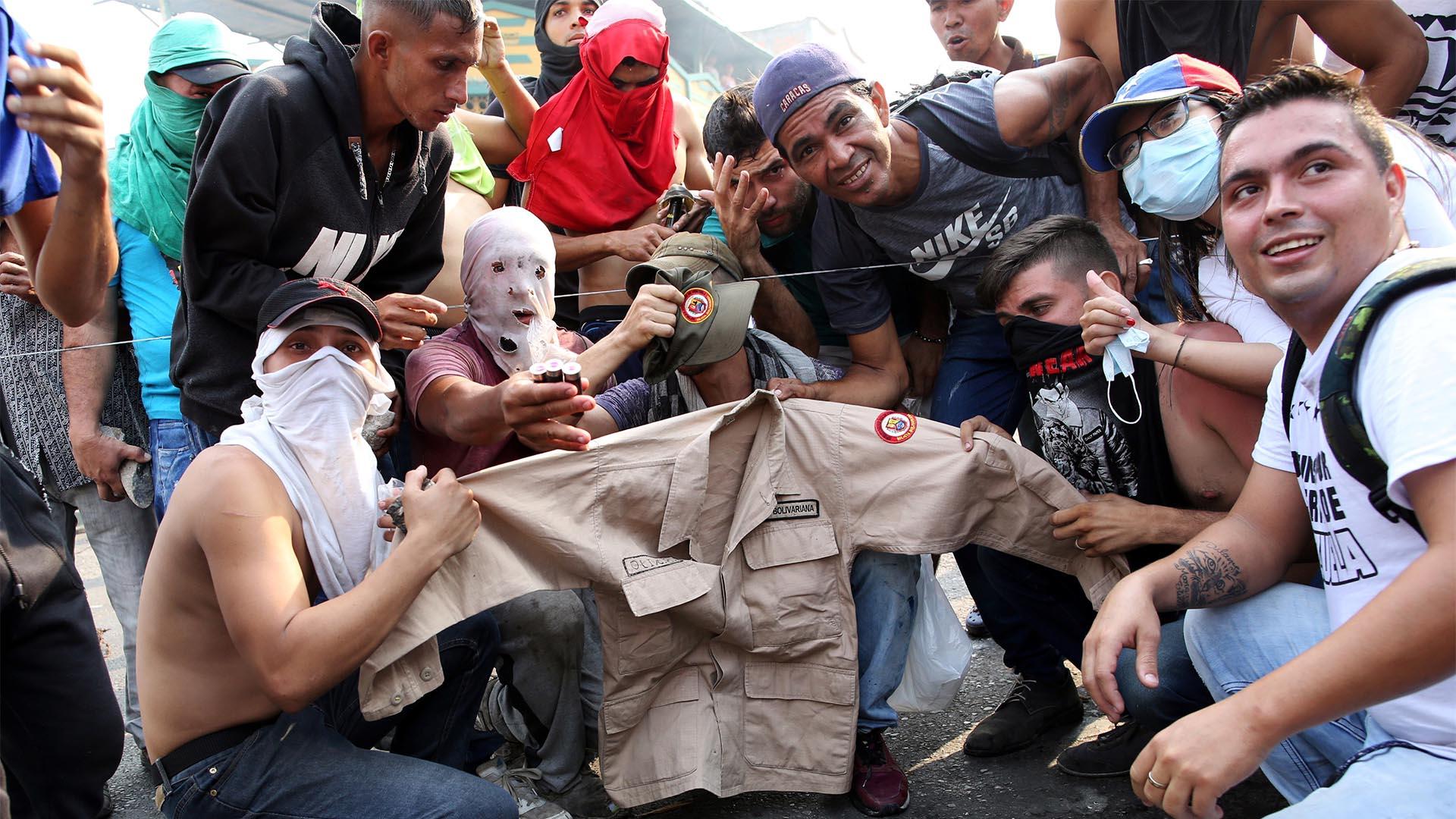 Manifestantes posan para una foto con la ropa de la milicia de un hombre venezolano mientras se enfrentan a las fuerzas de seguridad en Urena, Venezuela (Reuters)