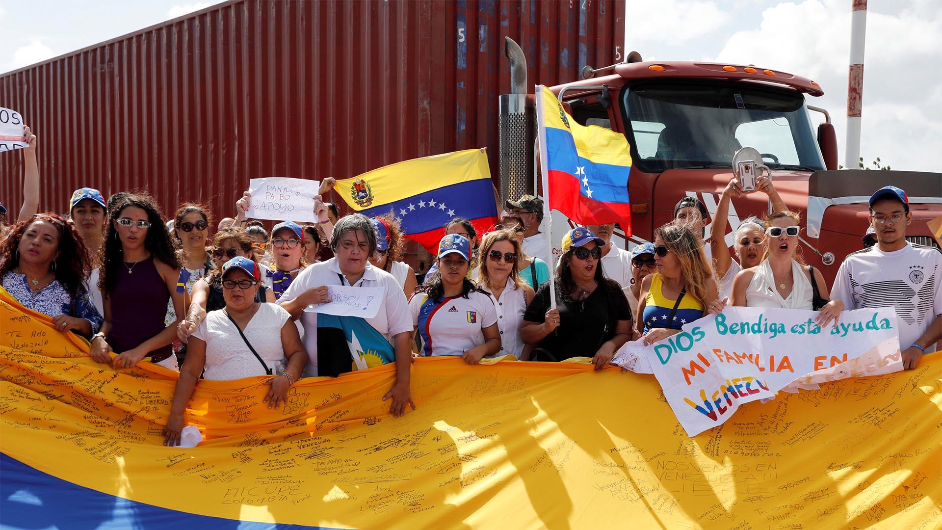 Los simpatizantes del líder opositor de Venezuela, Juan Guaido, sostienen banderas y firmas que respaldan la ayuda humanitaria en el puerto de Willemstad en la isla de Curazao (Reuters)