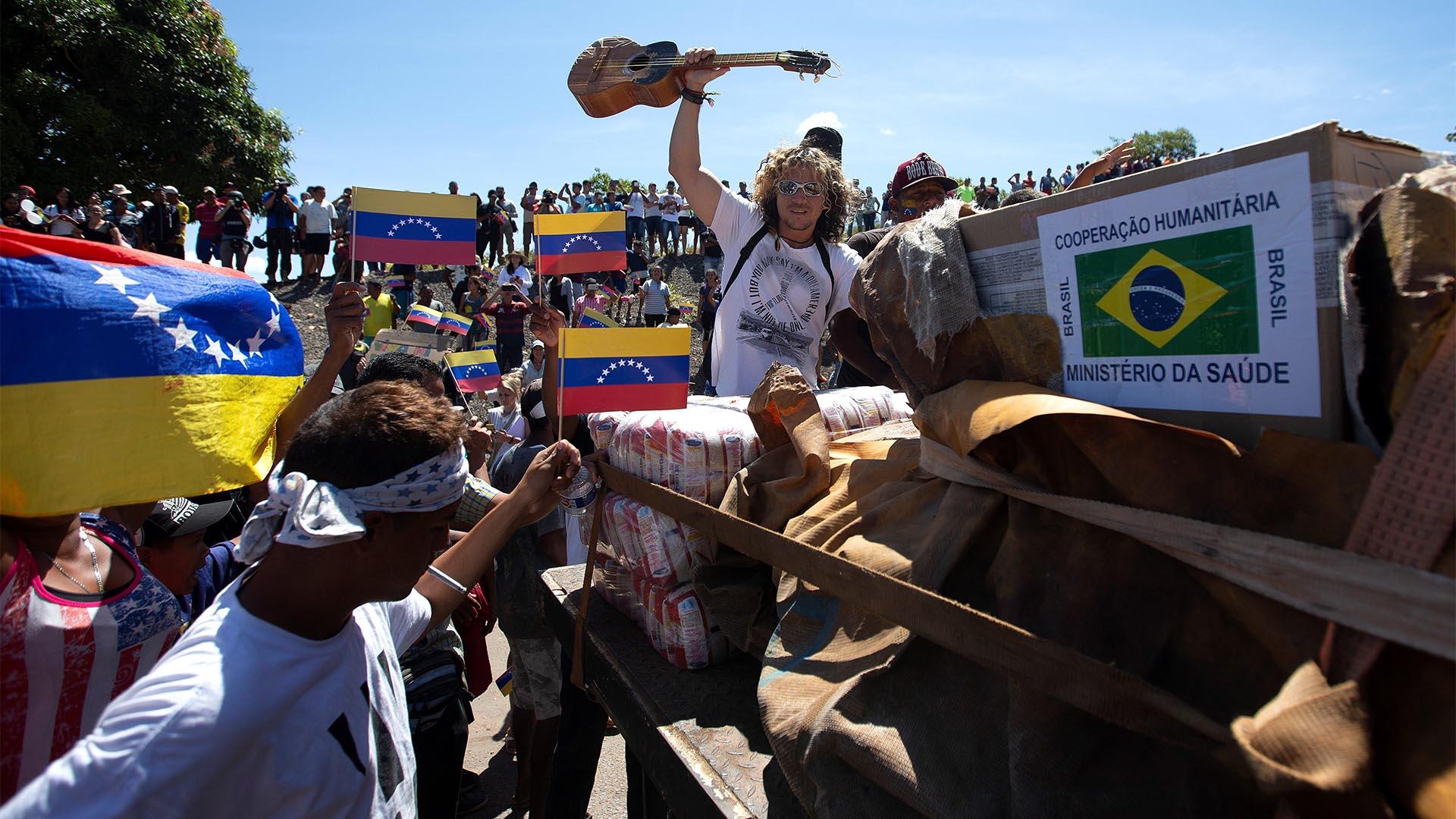 Personas celebran este sábado la llegada de la primera de las dos grandes cámaras con la ayuda humanitaria de Brasil a la localidad de Pacaraima, en el límite fronterizo entre ambos países, Cerrado desde el jueves por orden del régimen de Nicolás Maduro (EFE)